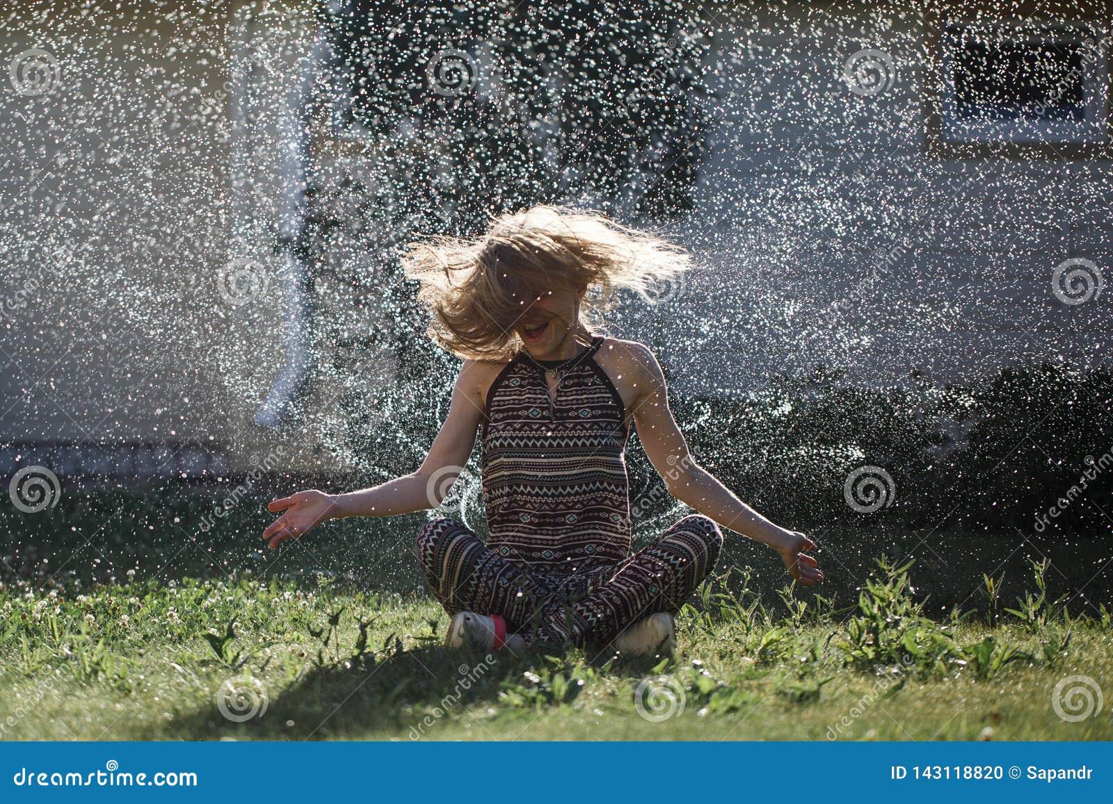 Junge Frau hat Spaß mit einem Spray des Wassers