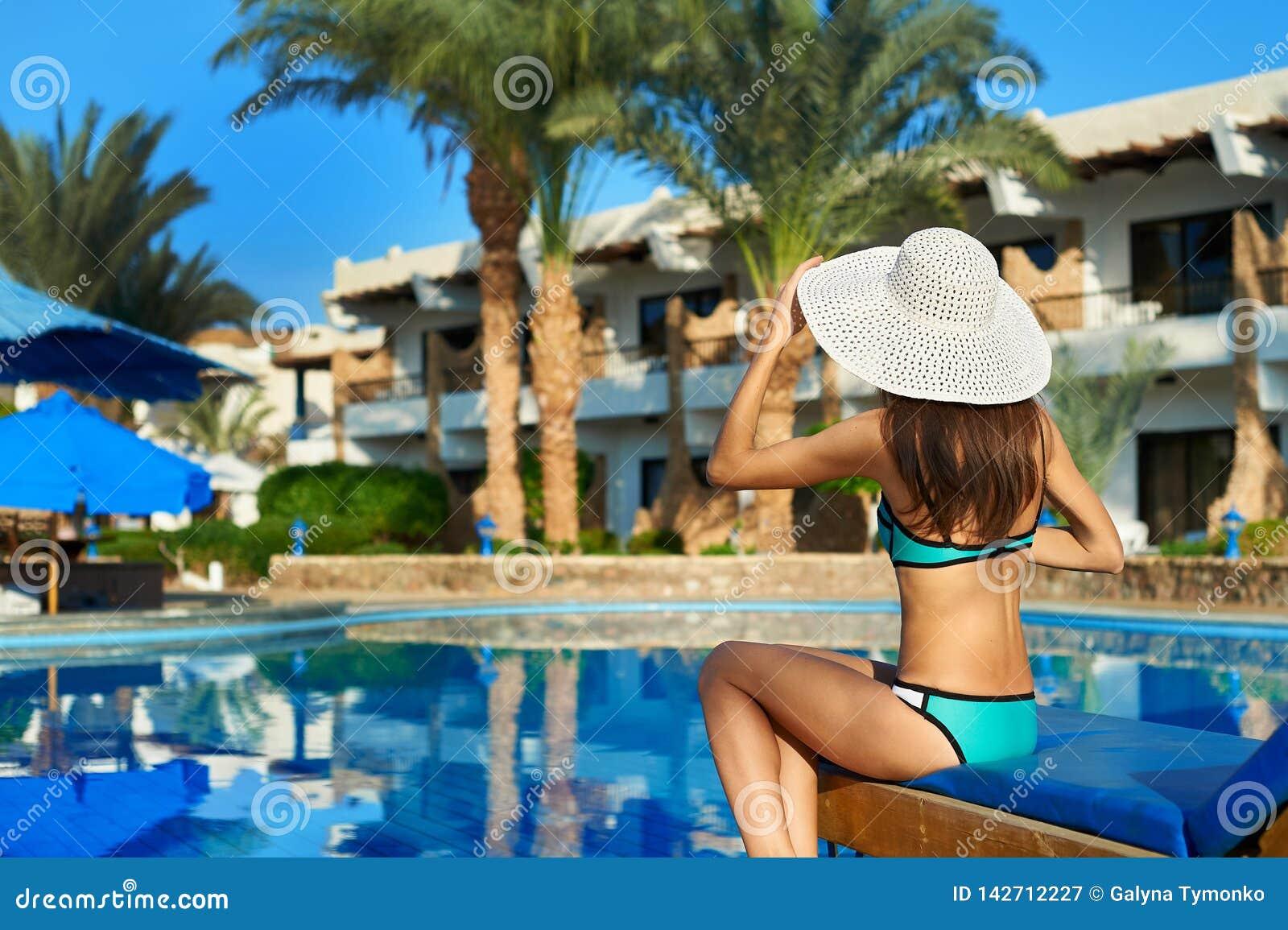 Junge Frau im Hut, der auf einem Sonnenruhesessel nahe Swimmingpool, Konzeptzeit zu reisen sitzt Entspannen Sie sich im Poolsomme