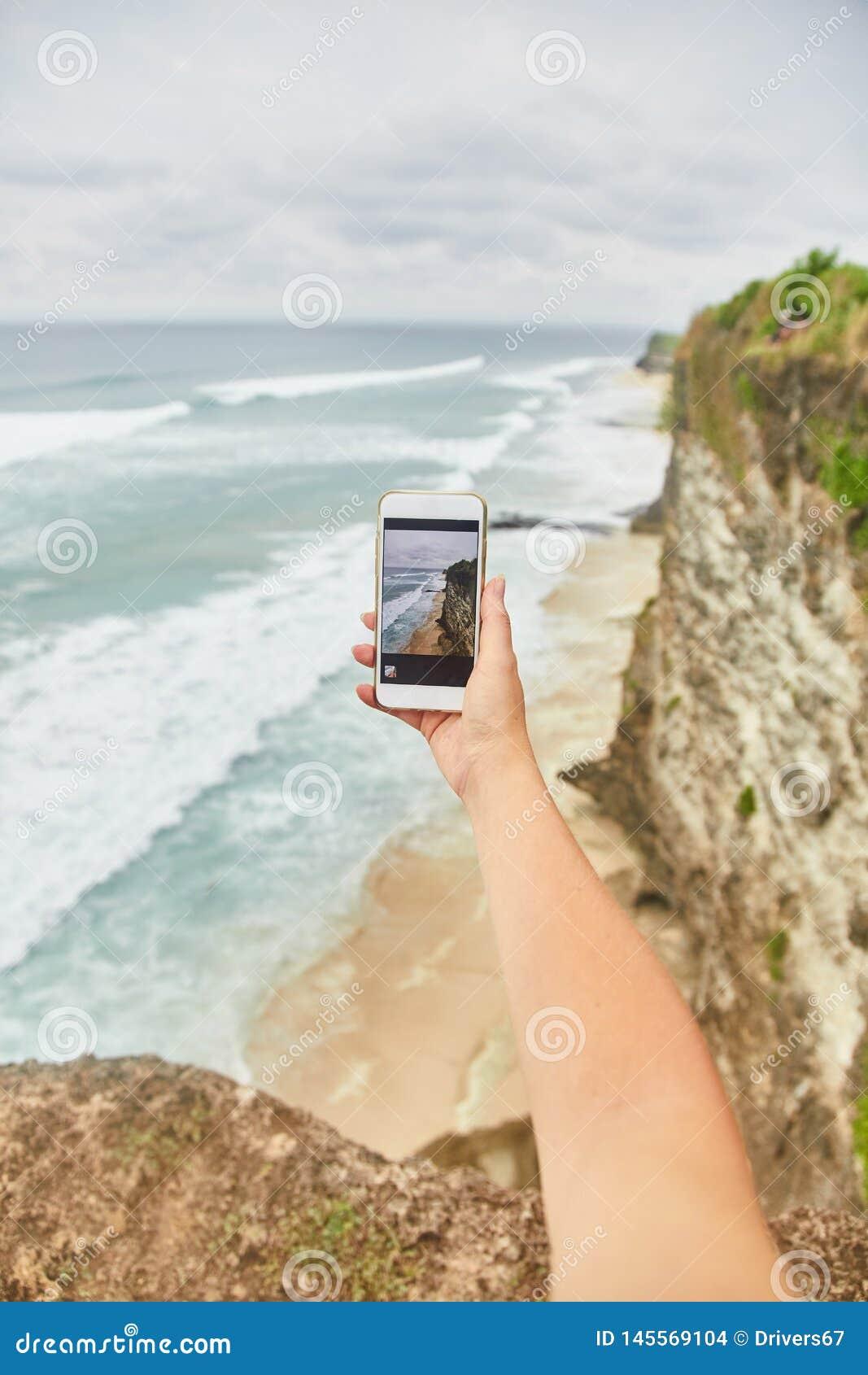 Junge Frau macht Fotos an ihrem Telefon Mädchen, das Fotos einer Landschaft macht