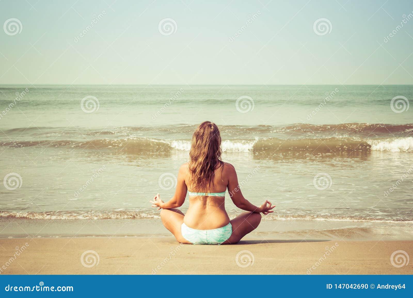 Junge Frau meditiert, sitzend auf dem Ozean