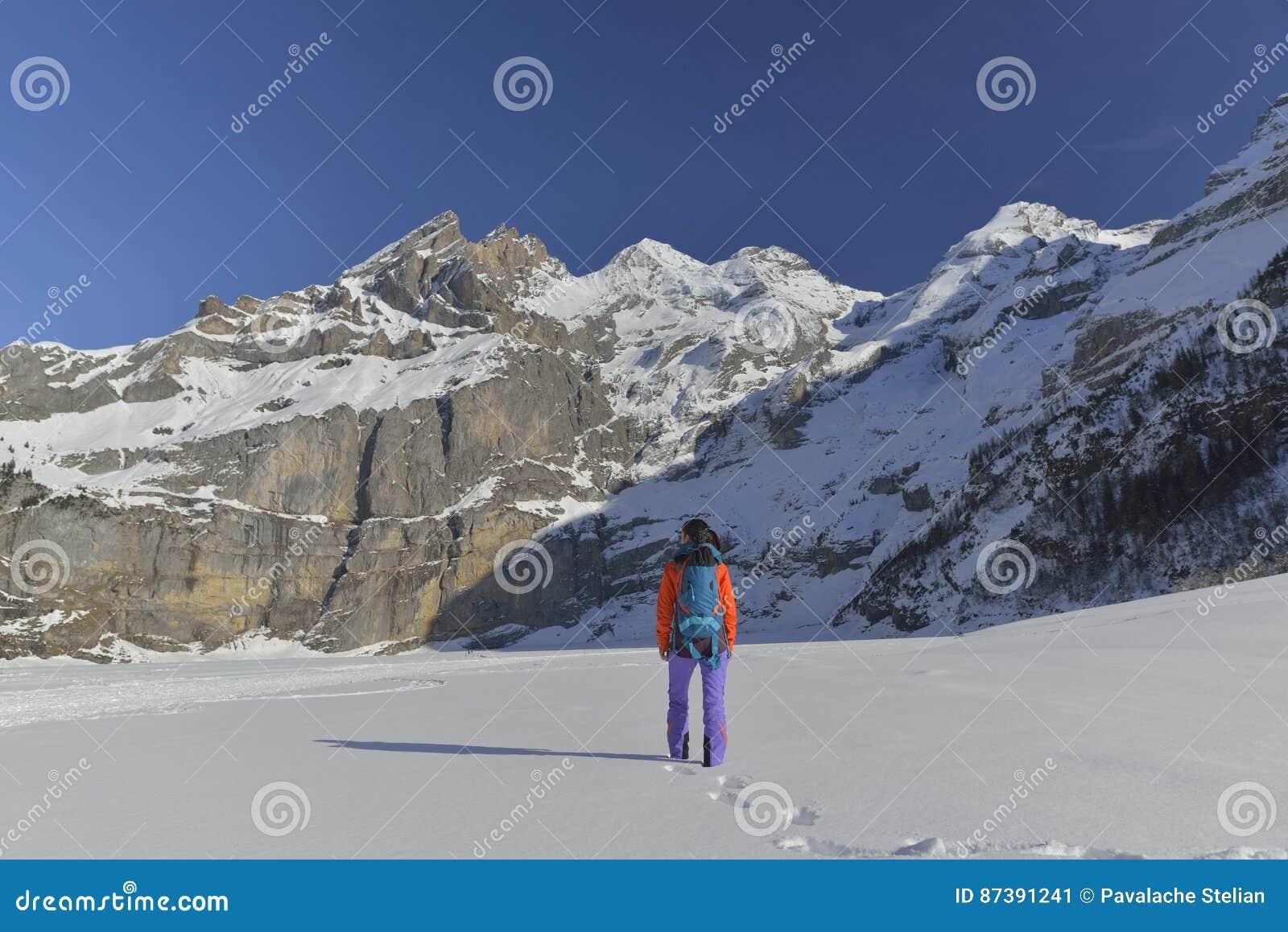 Junge Frau mit dem Rucksack, der in den Bergen wandert
