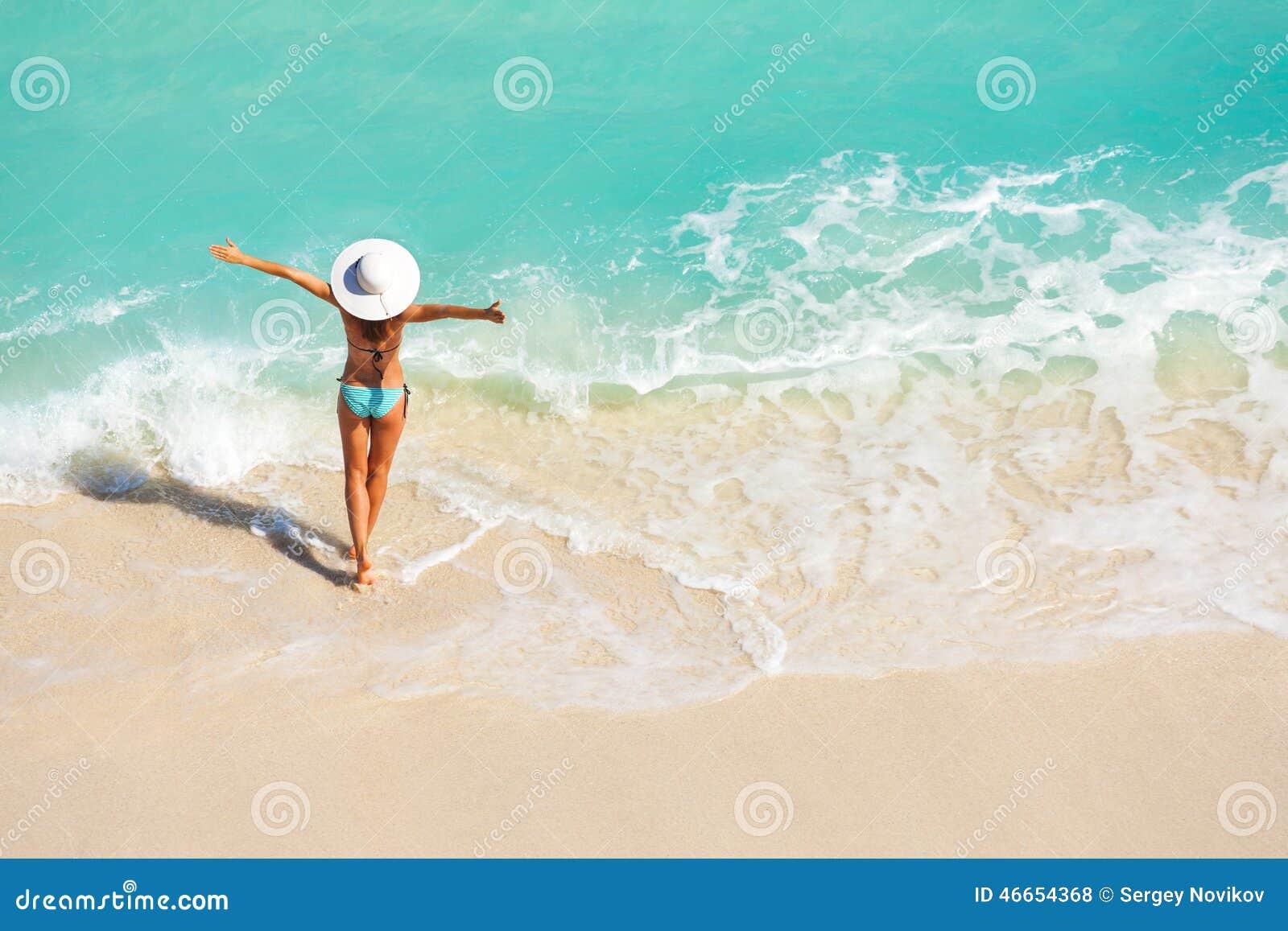Junge Frau mit den Armen auseinander auf Sandstrand