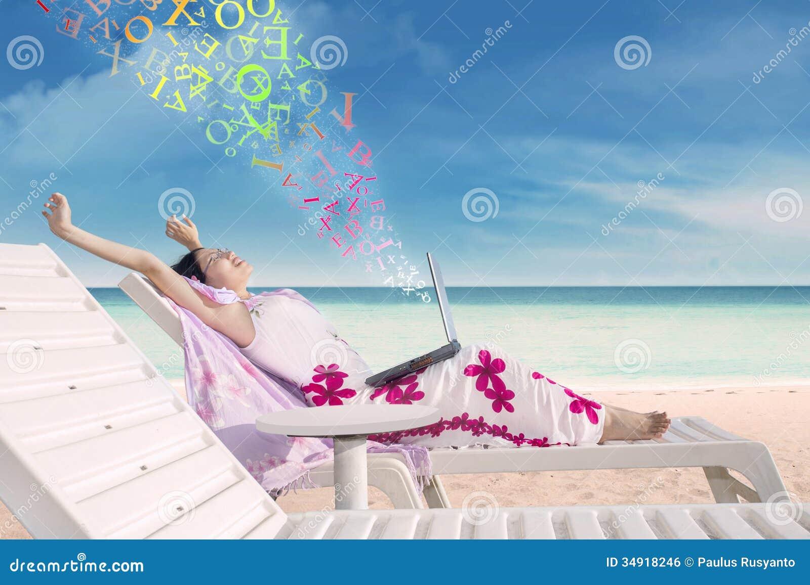 Junge Frau mit einem Laptop auf dem tropischen Strand