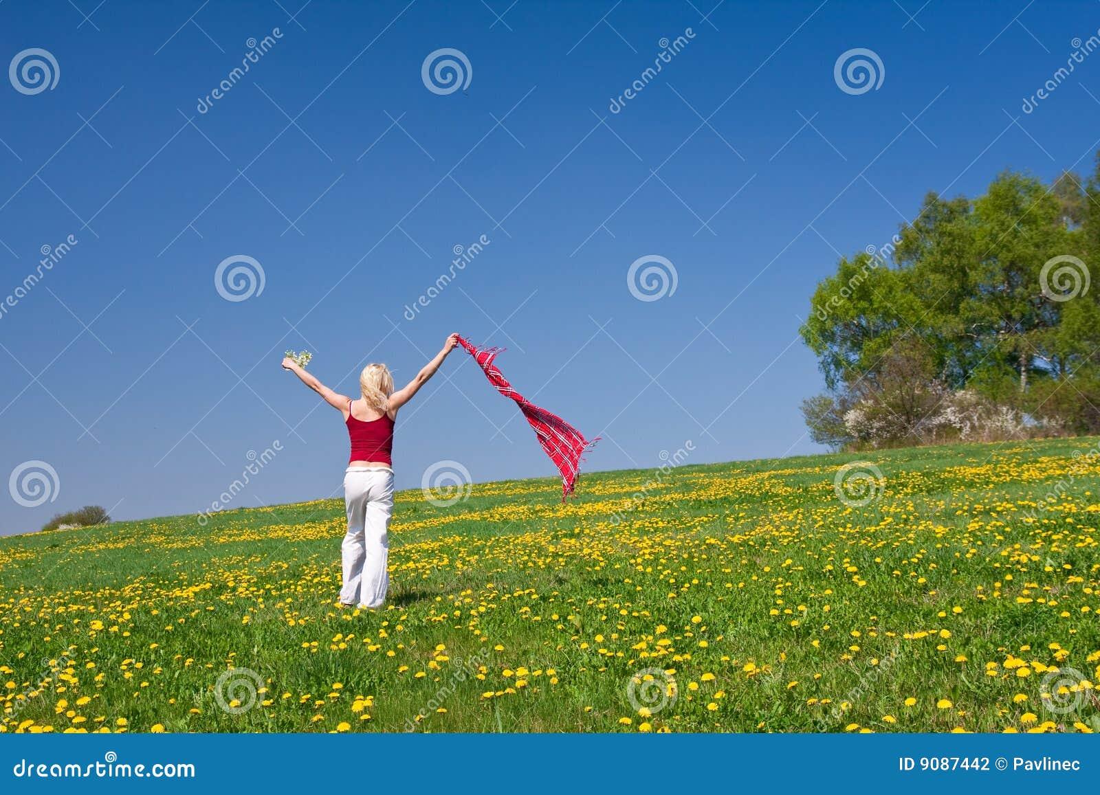 Junge Frau mit einem roten Schal auf einer Wiese