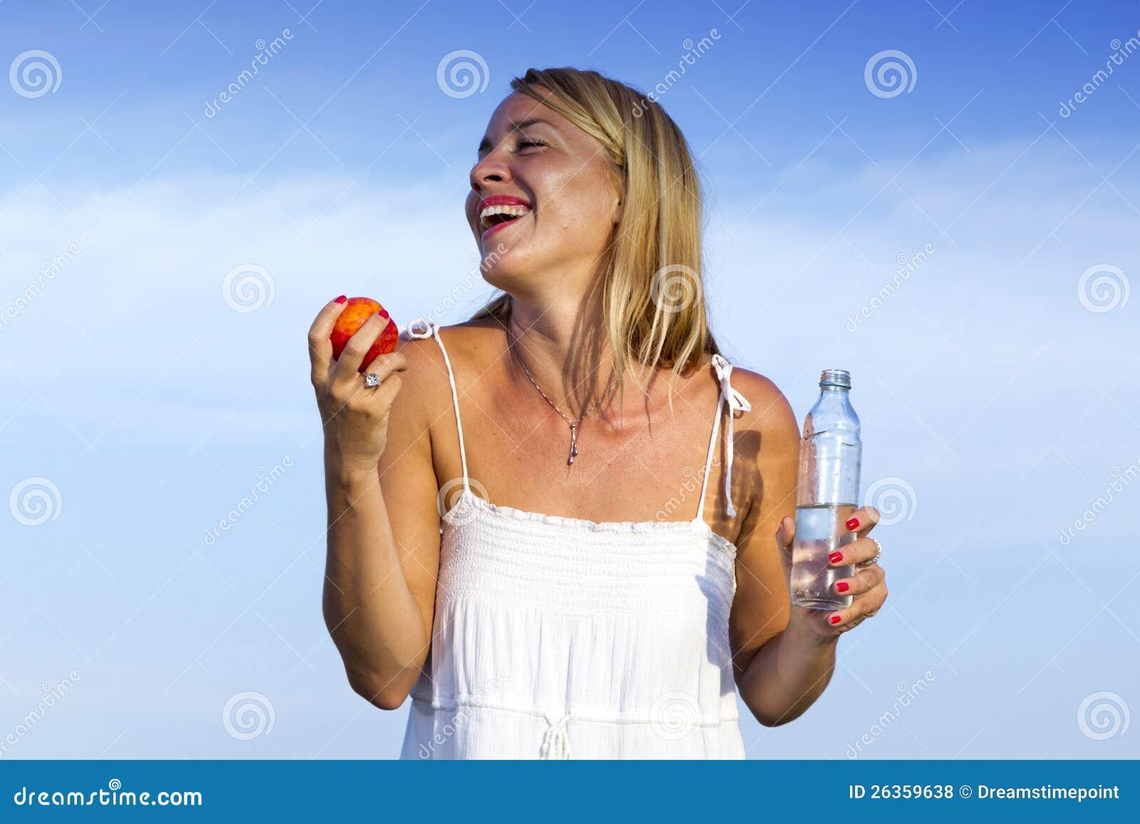 Junge Frau mit Flasche und Frucht in der Hand