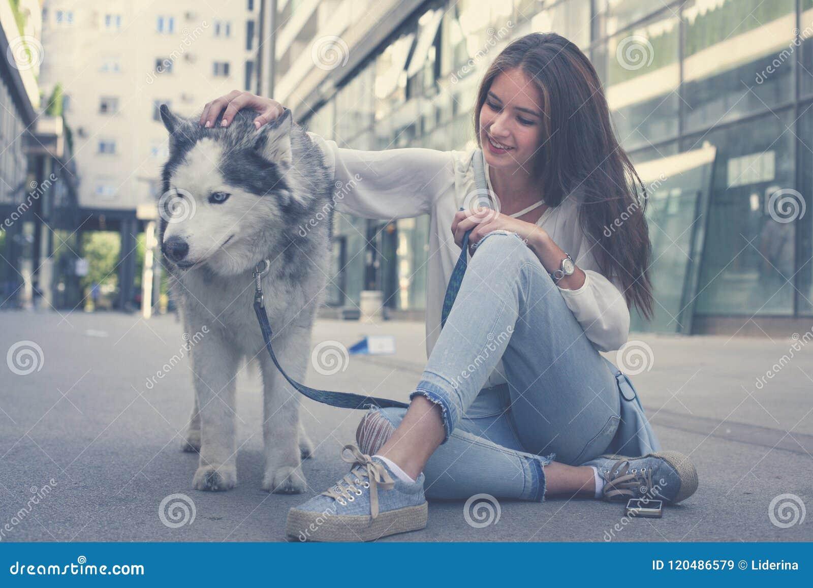 Junge Frau mit Hund in der Stadt Jugendlichmädchen mit ihrem Hund
