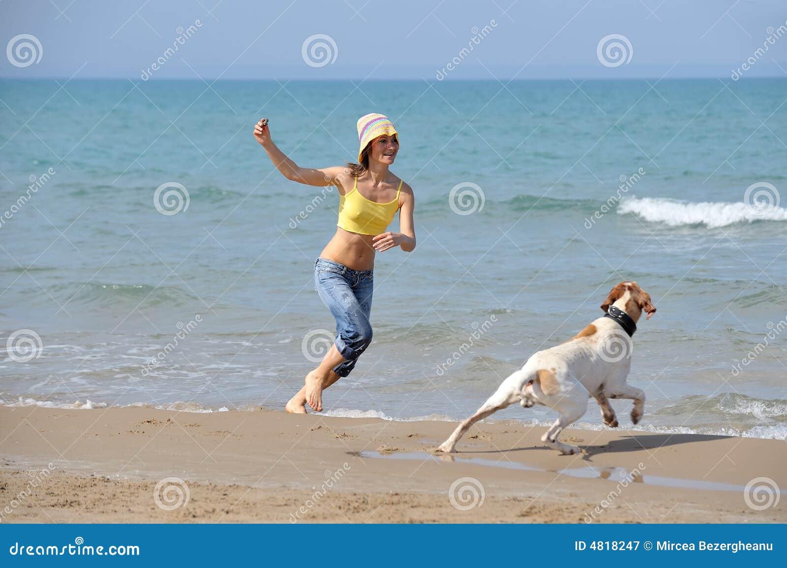 Junge Frau mit ihrem Hund auf dem Strand