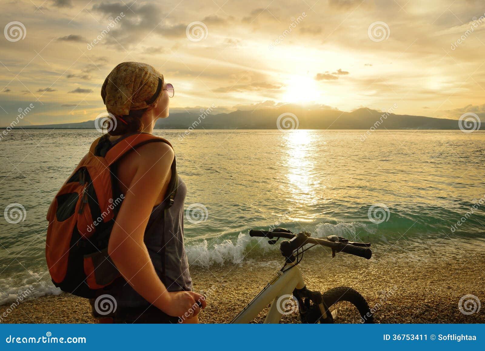 Junge Frau mit Rucksack, auf dem Ufer nahe seinem das Fahrrad stehend