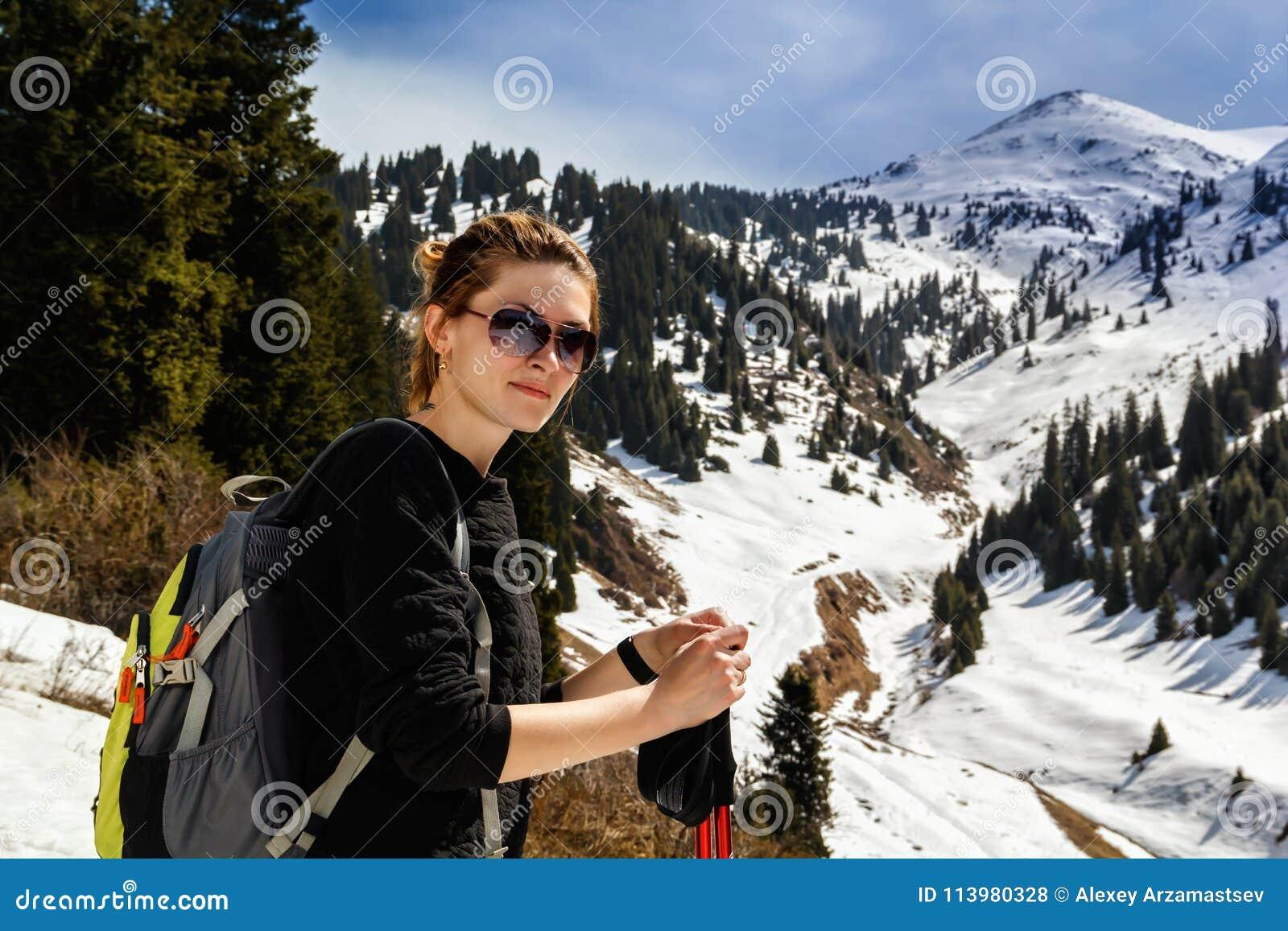Junge Frau mit Trekking haftet in mountainsYoung Frau mit Trekkingsstöcken
