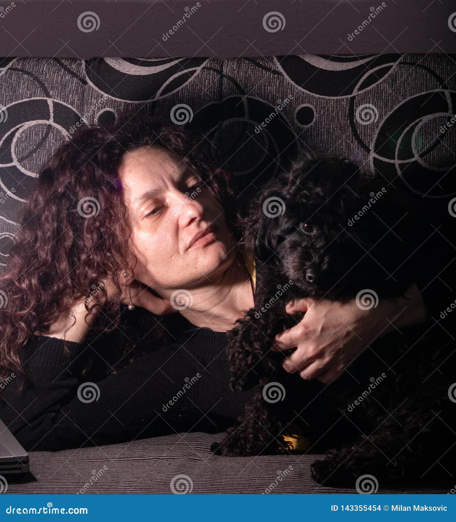 Junge Frau mit Zwergpudelhund auf einem Sofa in einer Dunkelkammer