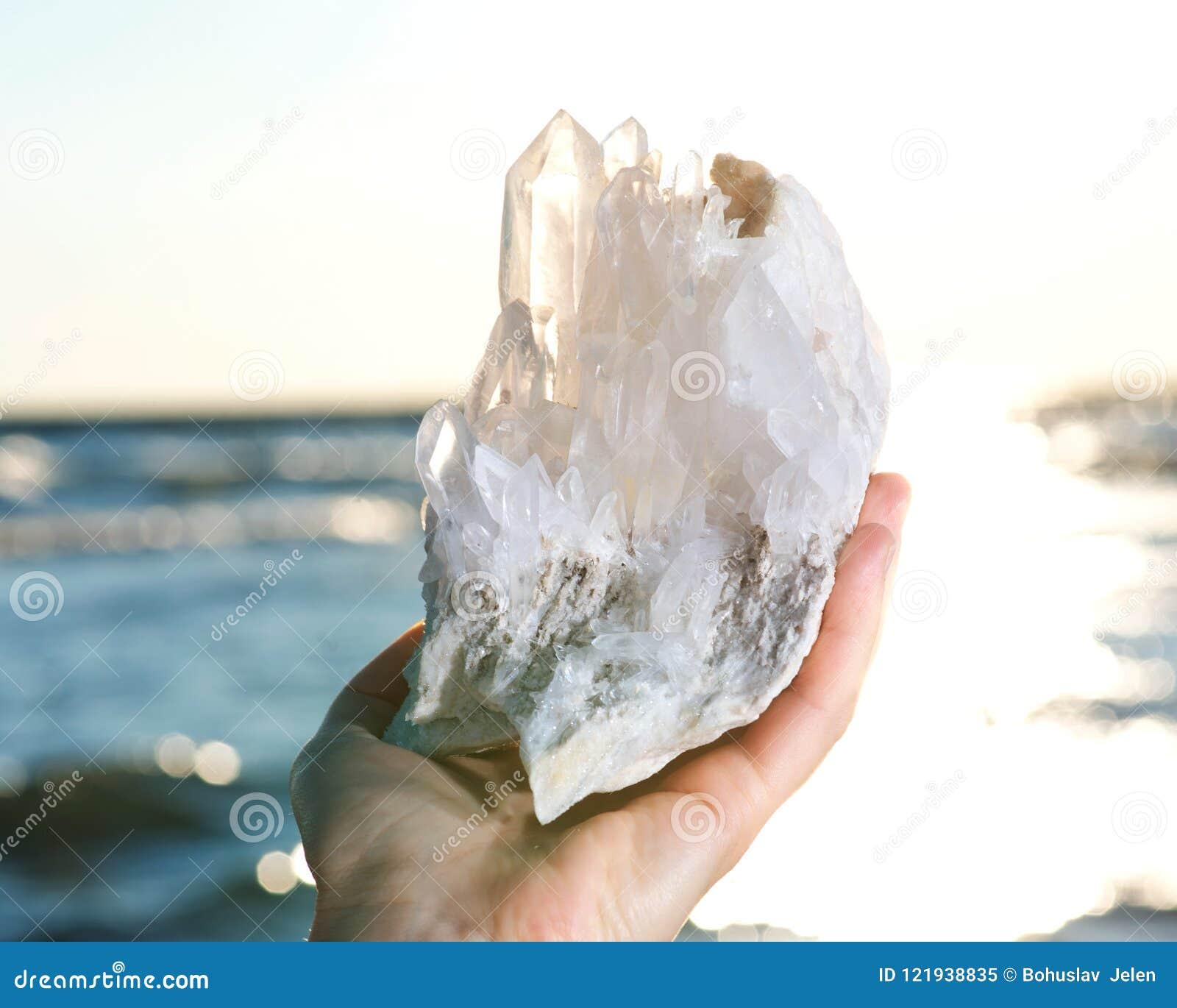 Junge Frau ` s Hand, die klare Quarz-Laser-Himalajagruppe hält