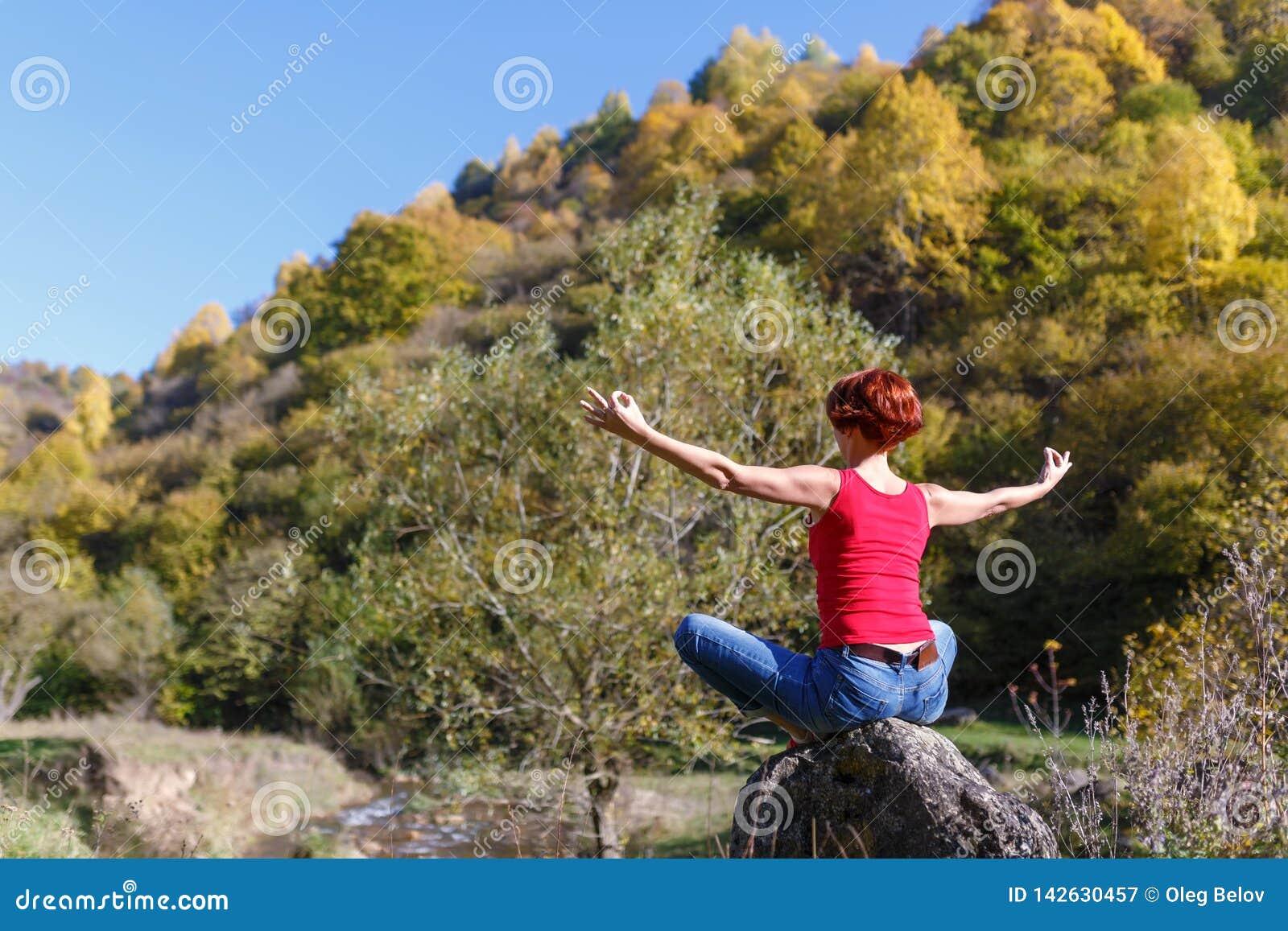 Junge Frau sitzt auf einem Stein und meditiert vor dem hintergrund eines Flusses, eines Waldes und eines blauen Himmels an einem