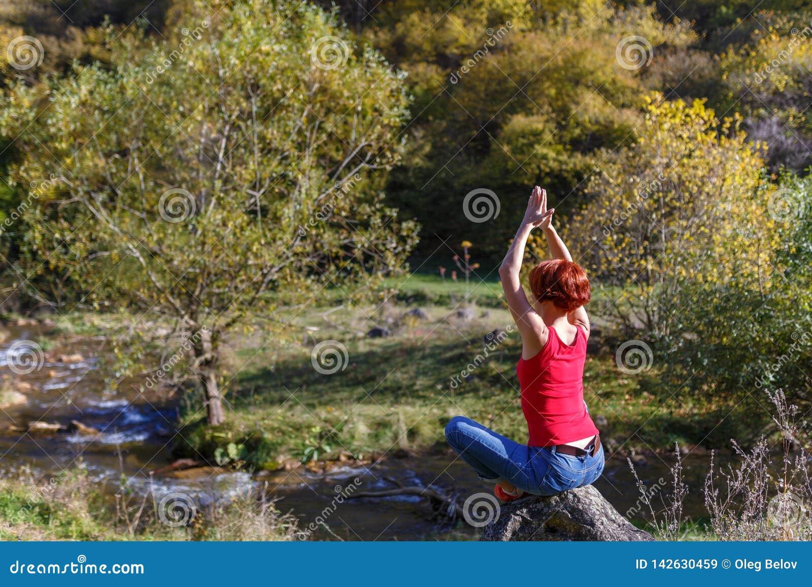 Junge Frau sitzt auf einem Stein und meditiert vor dem hintergrund eines Flusses und eines Waldes an einem sonnigen Herbsttag