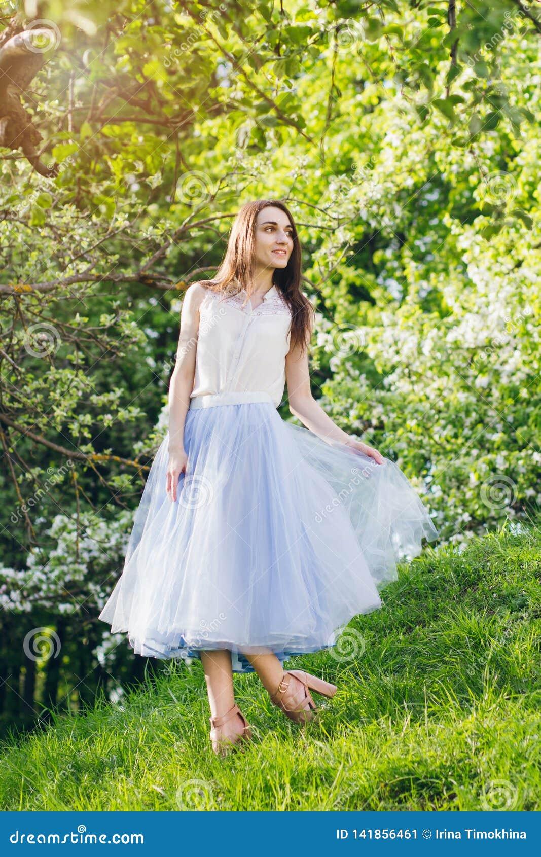 Junge Frau steht auf einem Hügel vor dem hintergrund der blühenden Bäume