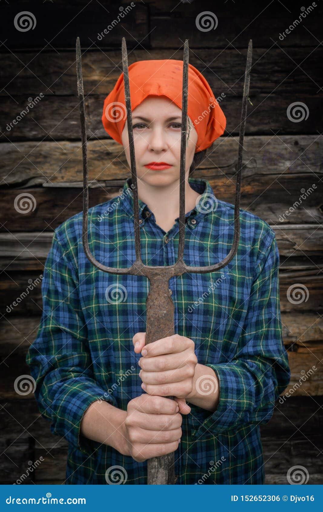 Junge Frau steht mit einer Heugabel nahe einem Stall auf einer Ranch