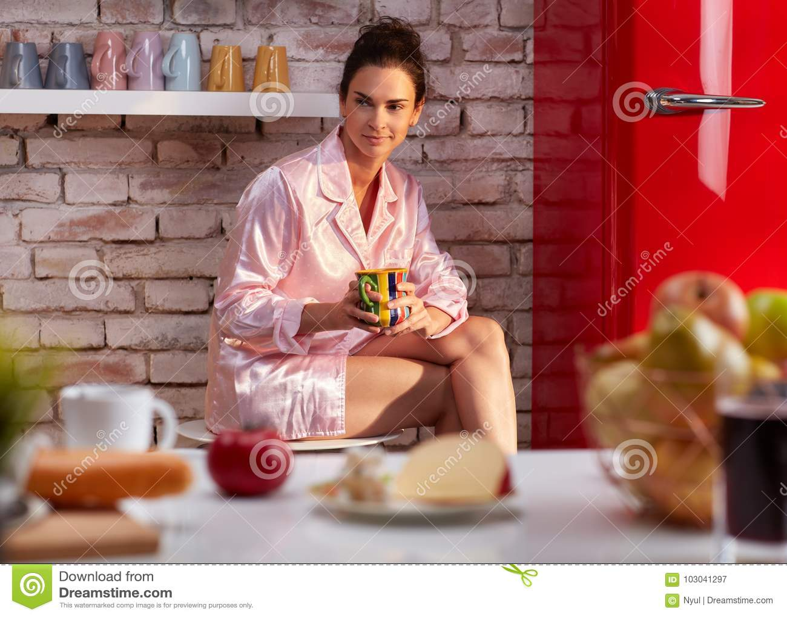 Junge Frau trinkt Frühstückskaffee im Pyjama