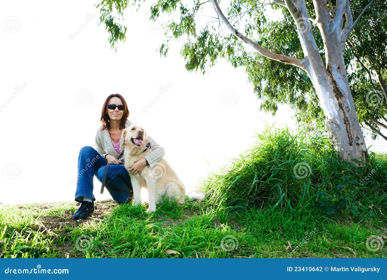 Junge Frau und goldener Apportierhund im Gras