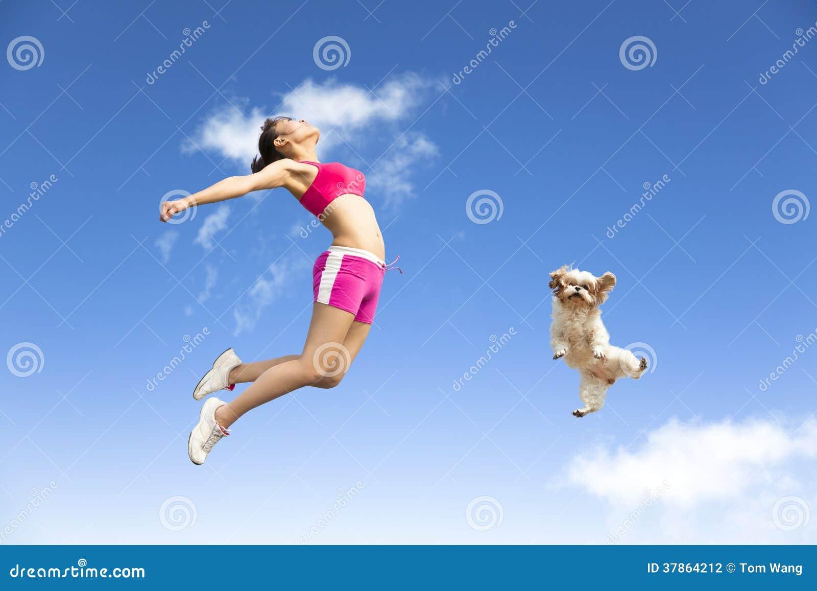 Junge Frau und Hund, die in den Himmel springt