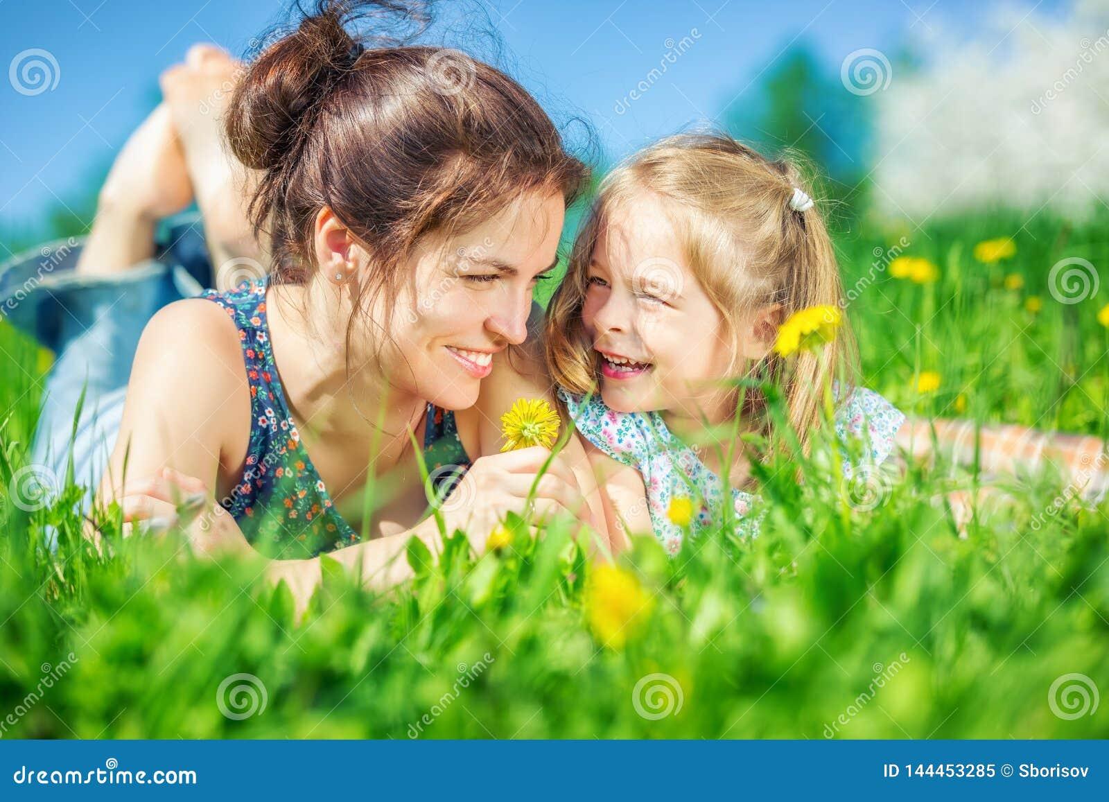Junge Frau und ihre Tochter auf grünem Sommergras