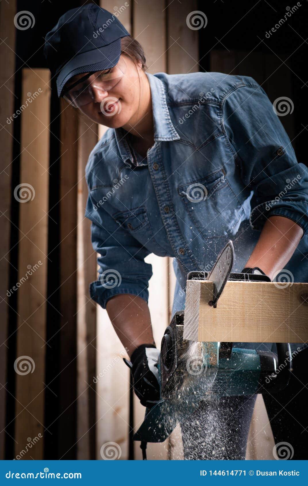 Junge Frau unter Verwendung der modernen elektrischen Säge in der Werkstatt