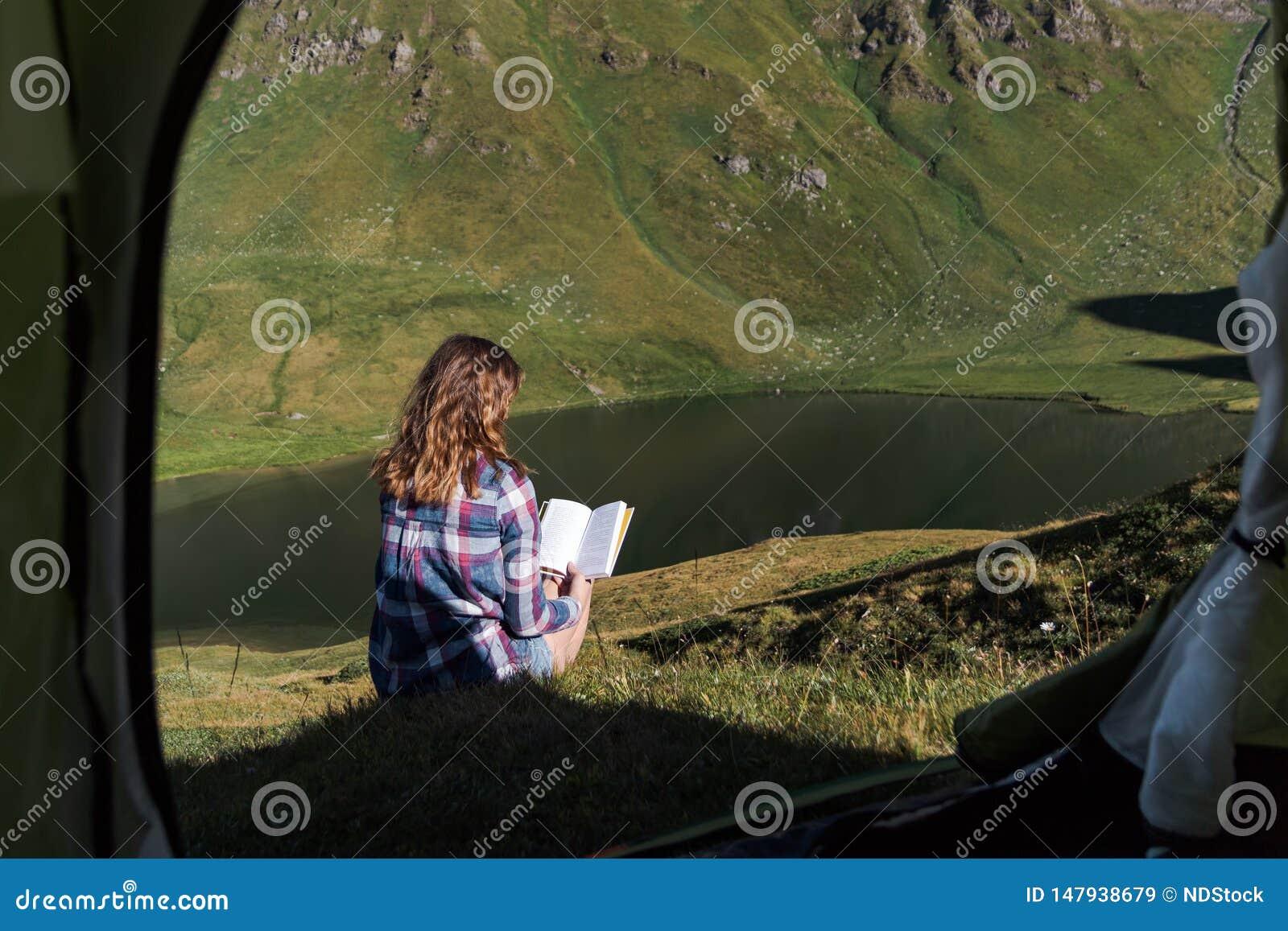 Junge Frau vor einem Zelt in den Schweizer Bergen ein Buch lesend