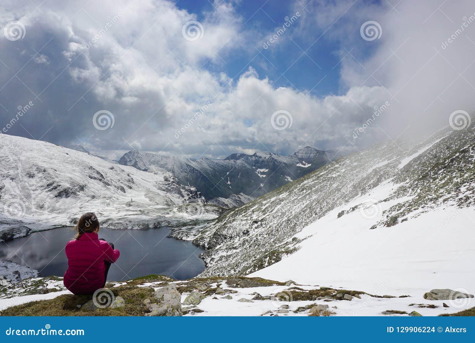 Junge Frau, welche die Ansicht in die Berge bewundert