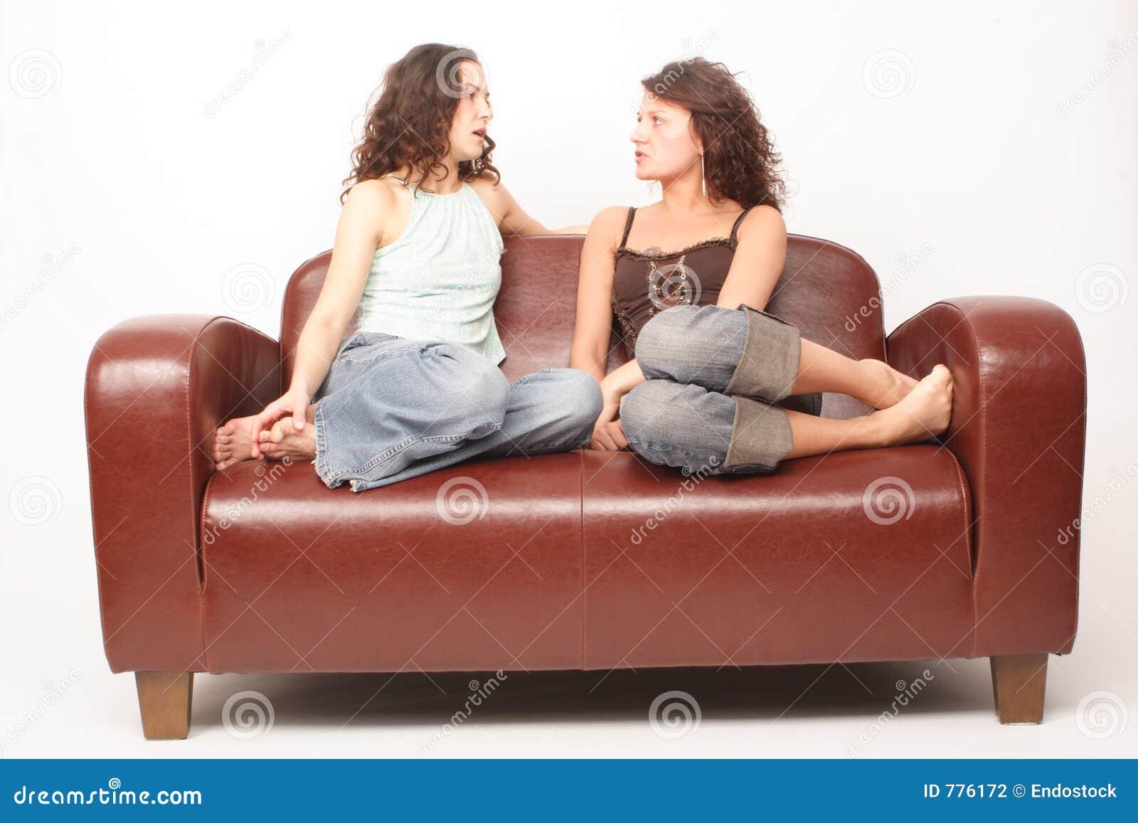 Junge Frauen Die Auf Sofa Und Der Unterhaltung Sitzen