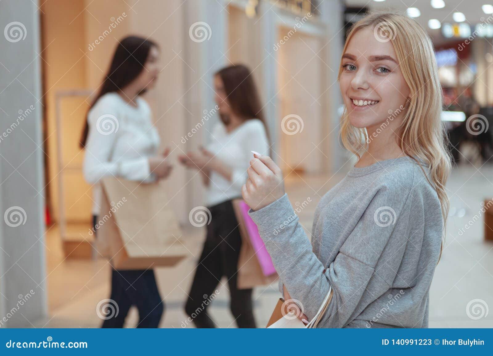 Junge Frauen, die zusammen im Einkaufszentrum kaufen genießen