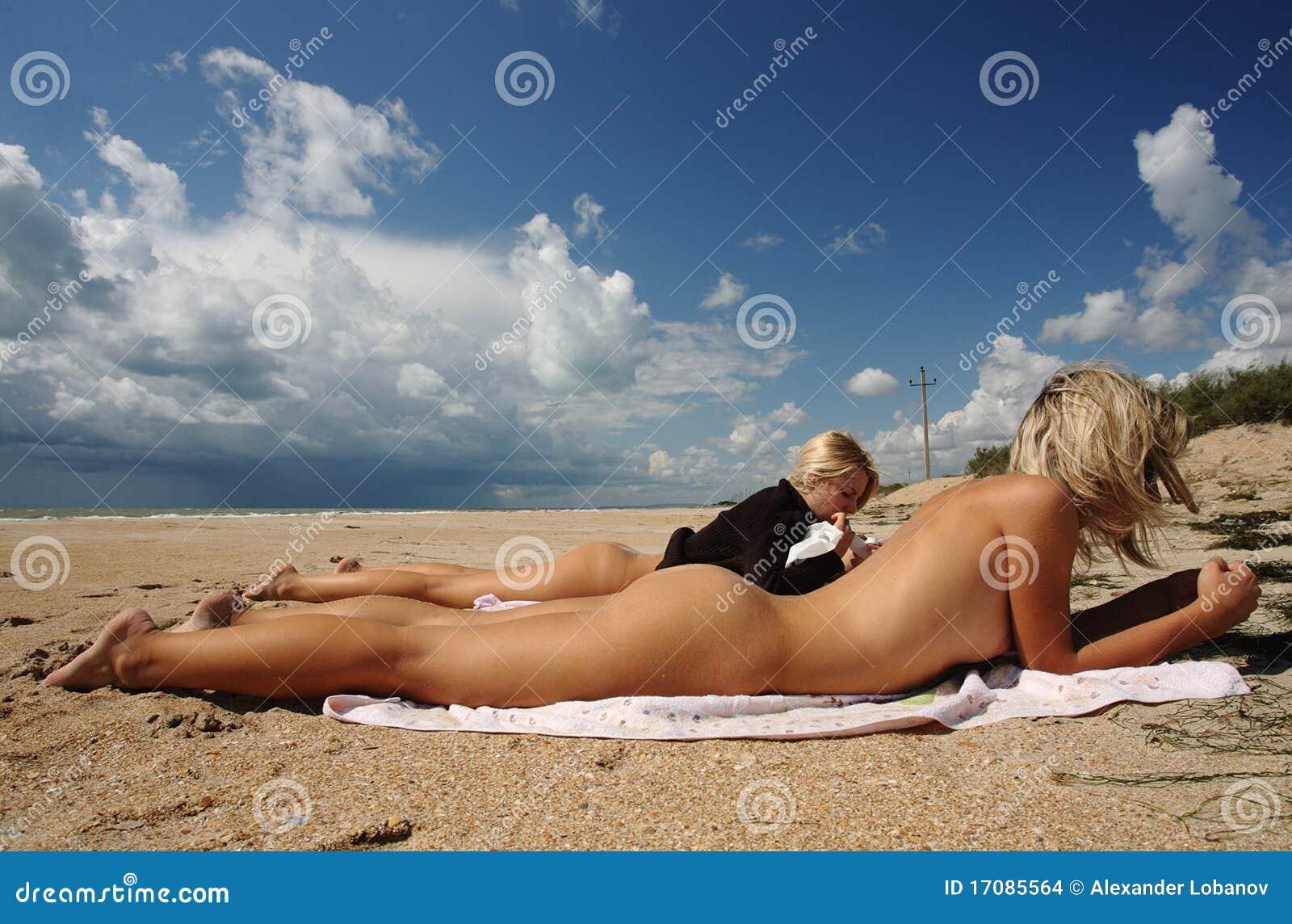 Junge Frauen nehmen auf dem sandigen Strand ein Sonnenbad.