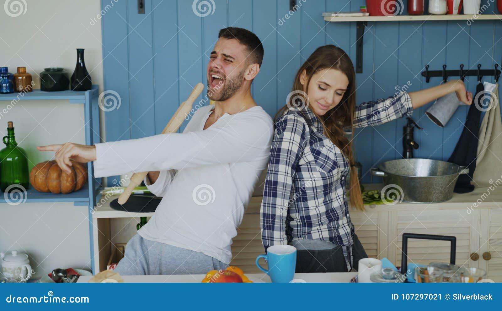 Junge frohe Paare haben Spaßtanzen und den Gesang, während sie zu Hause der Tabelle zum Frühstück in der Küche eingestellt werden