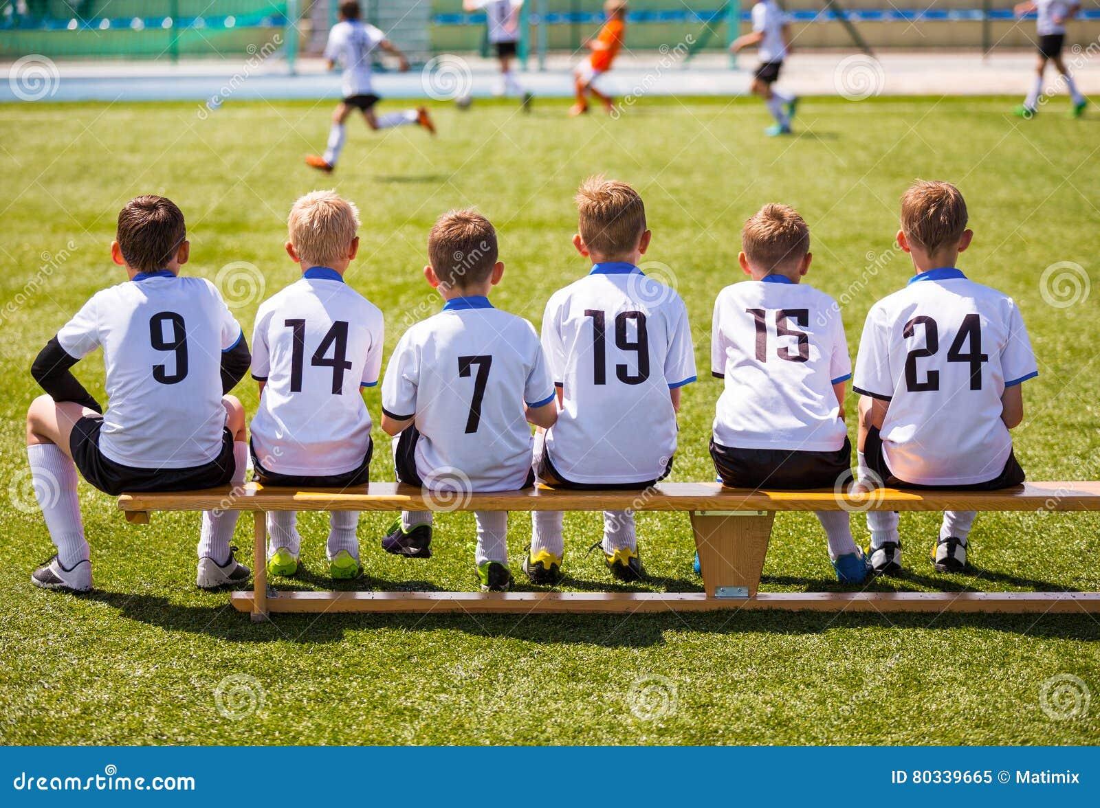 Junge Fußball-Spieler Junger Fußball Team Sitting auf Holzbank