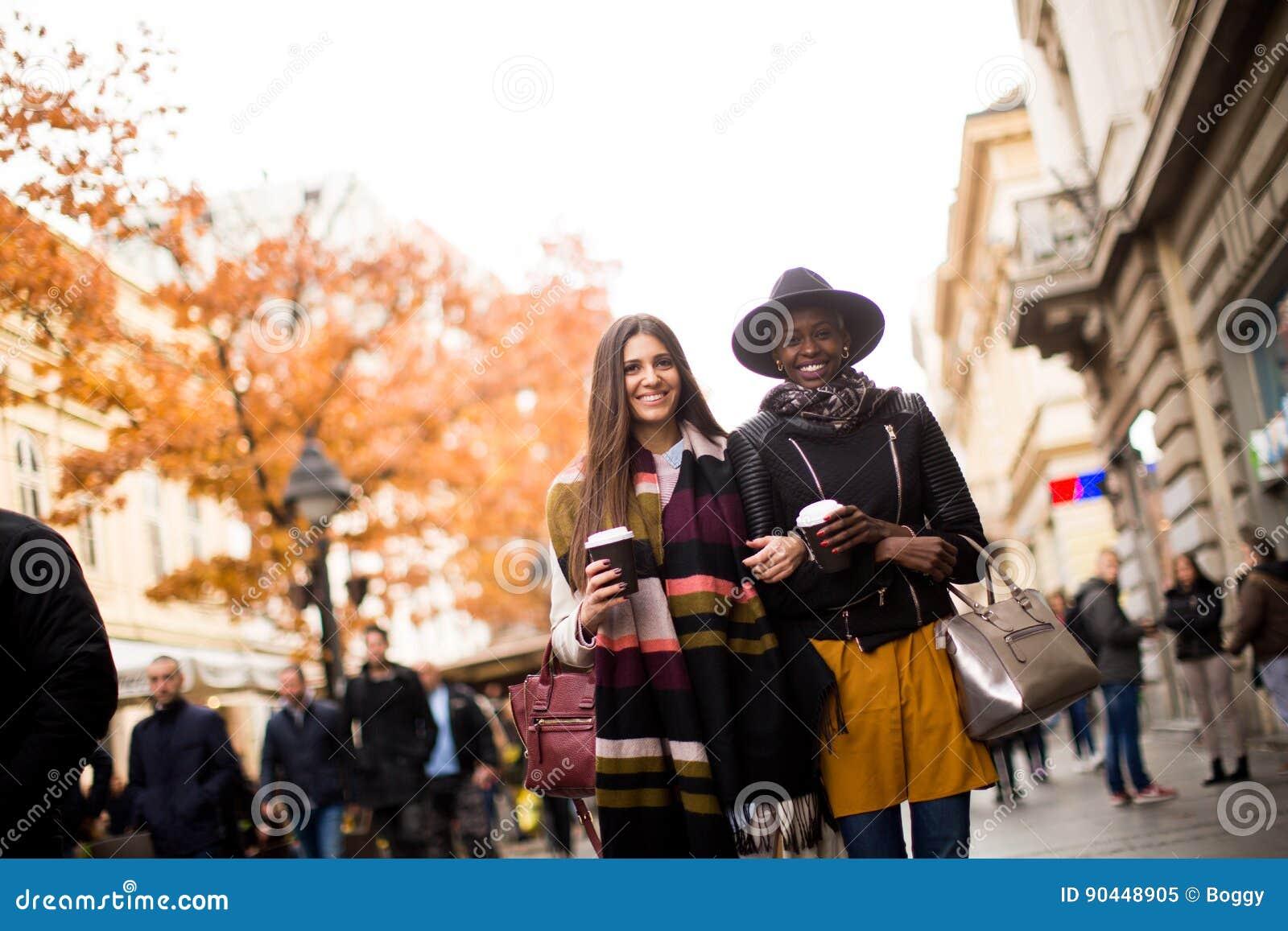 Junge gemischtrassige Freunde, die um die Stadt gehen