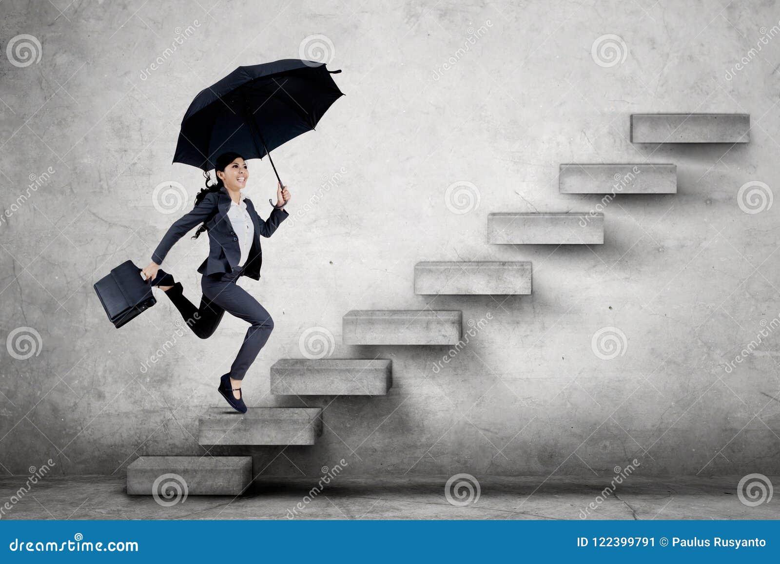 Junge Geschäftsfrau, die auf dem Treppenhaus läuft