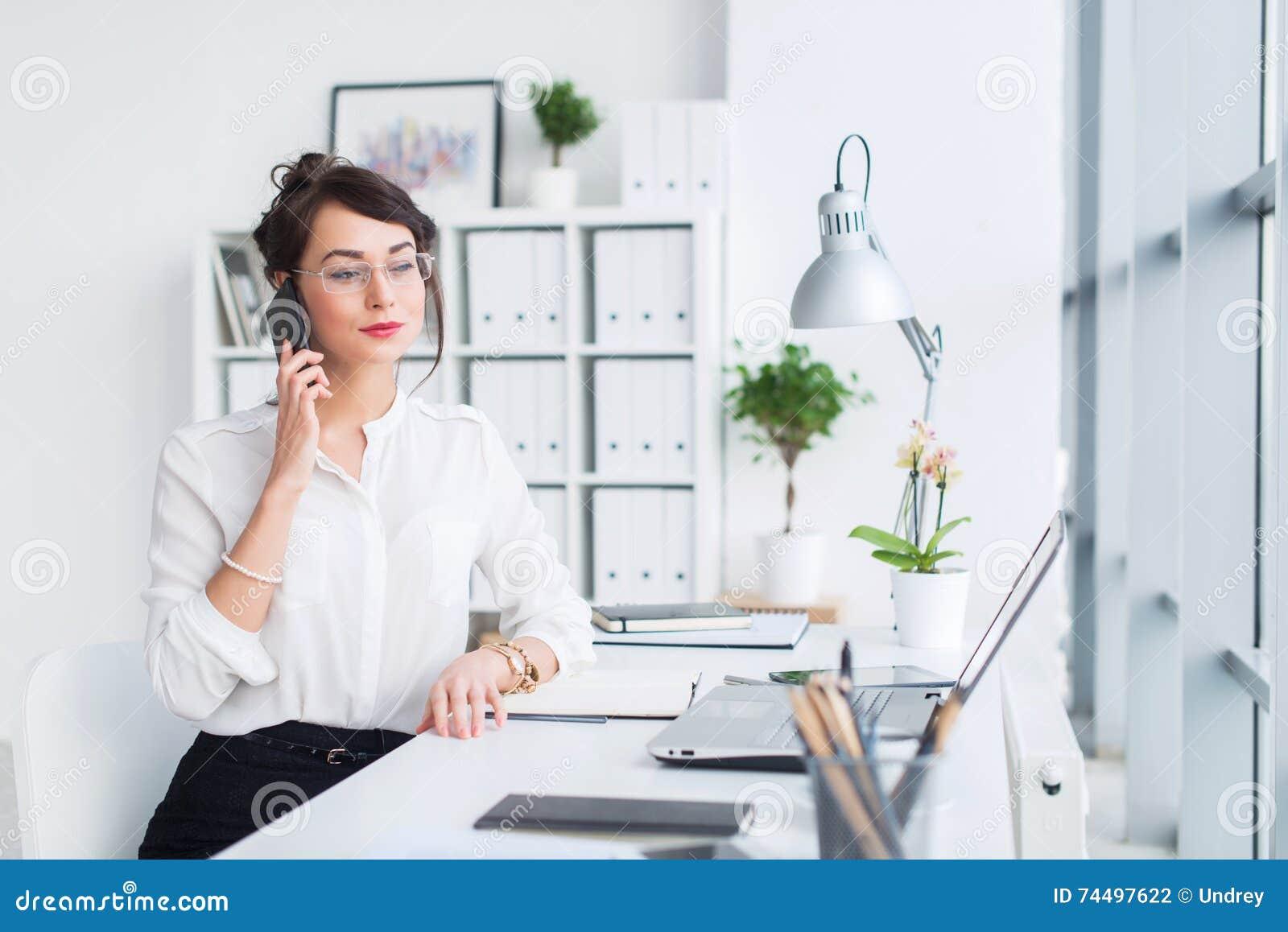 Junge Geschäftsfrau, die im Büro, schreibend, unter Verwendung des Computers arbeitet Starke Frau, die online Informationen sucht
