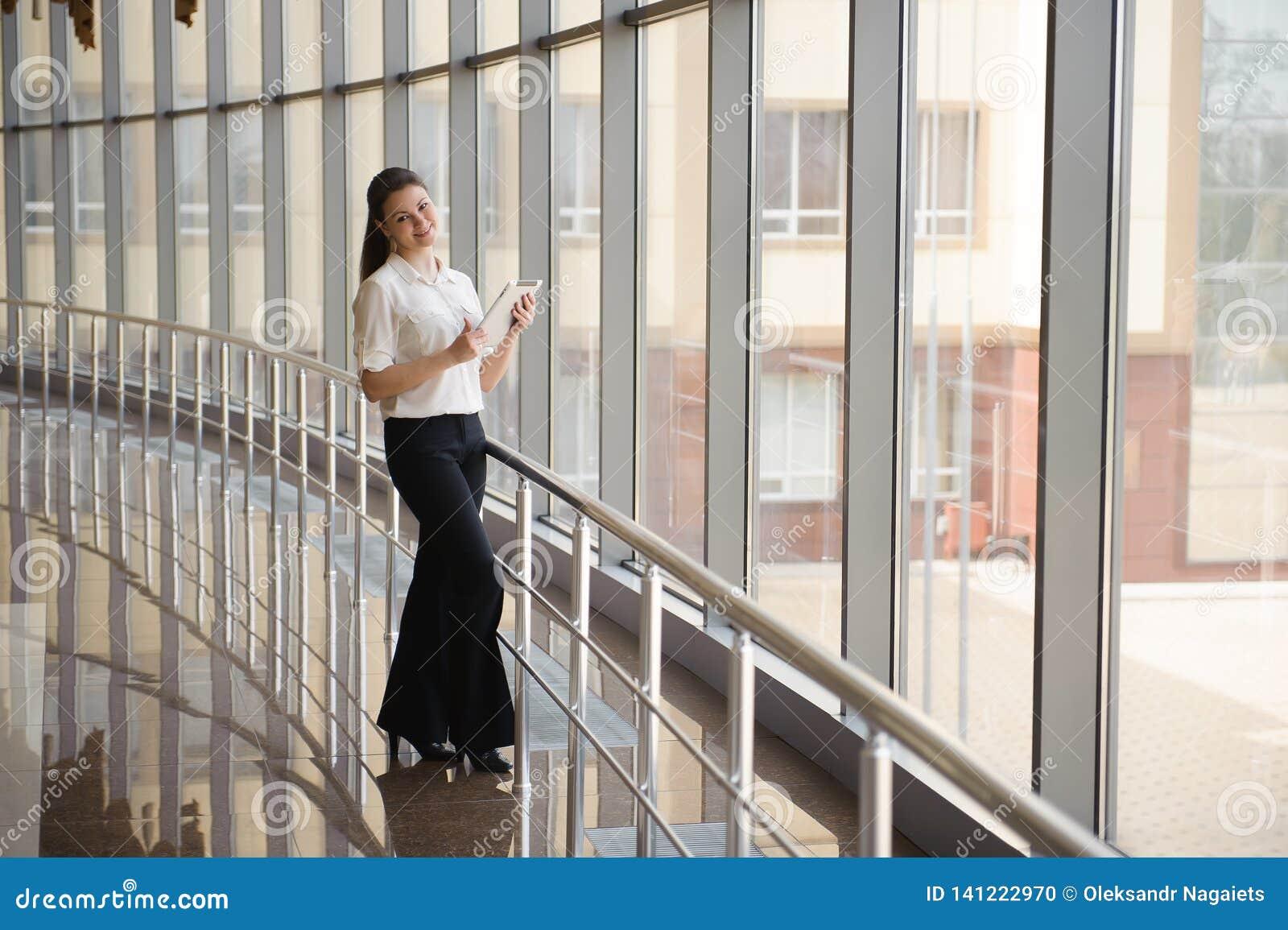 Junge Geschäftsfrau, die an ipad beim Bereitstehen des Fensters im Büro arbeitet Schönes junges weibliches Modell im hellen Büro