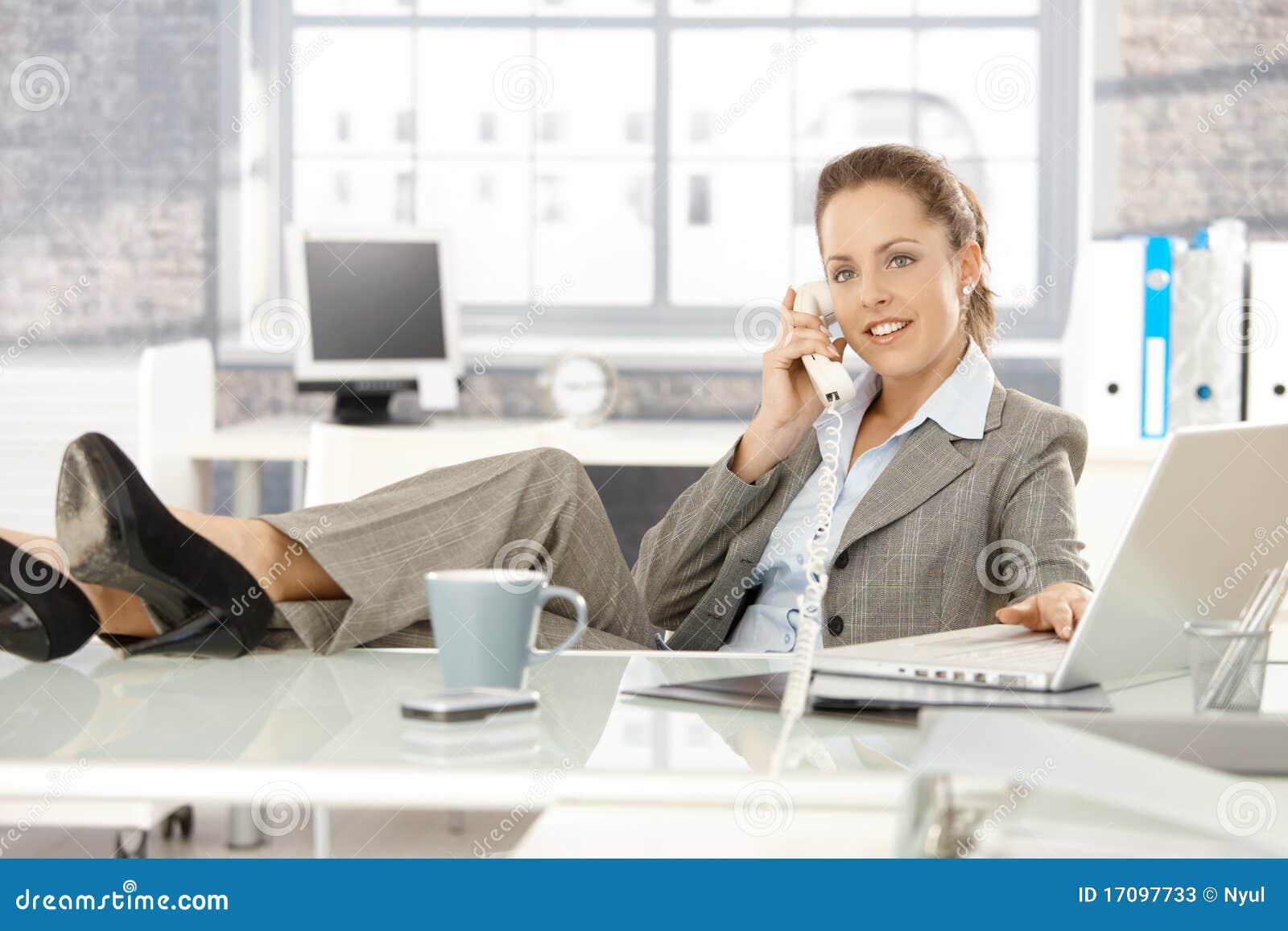 Junge Geschäftsfrau, die am Telefon im Büro spricht