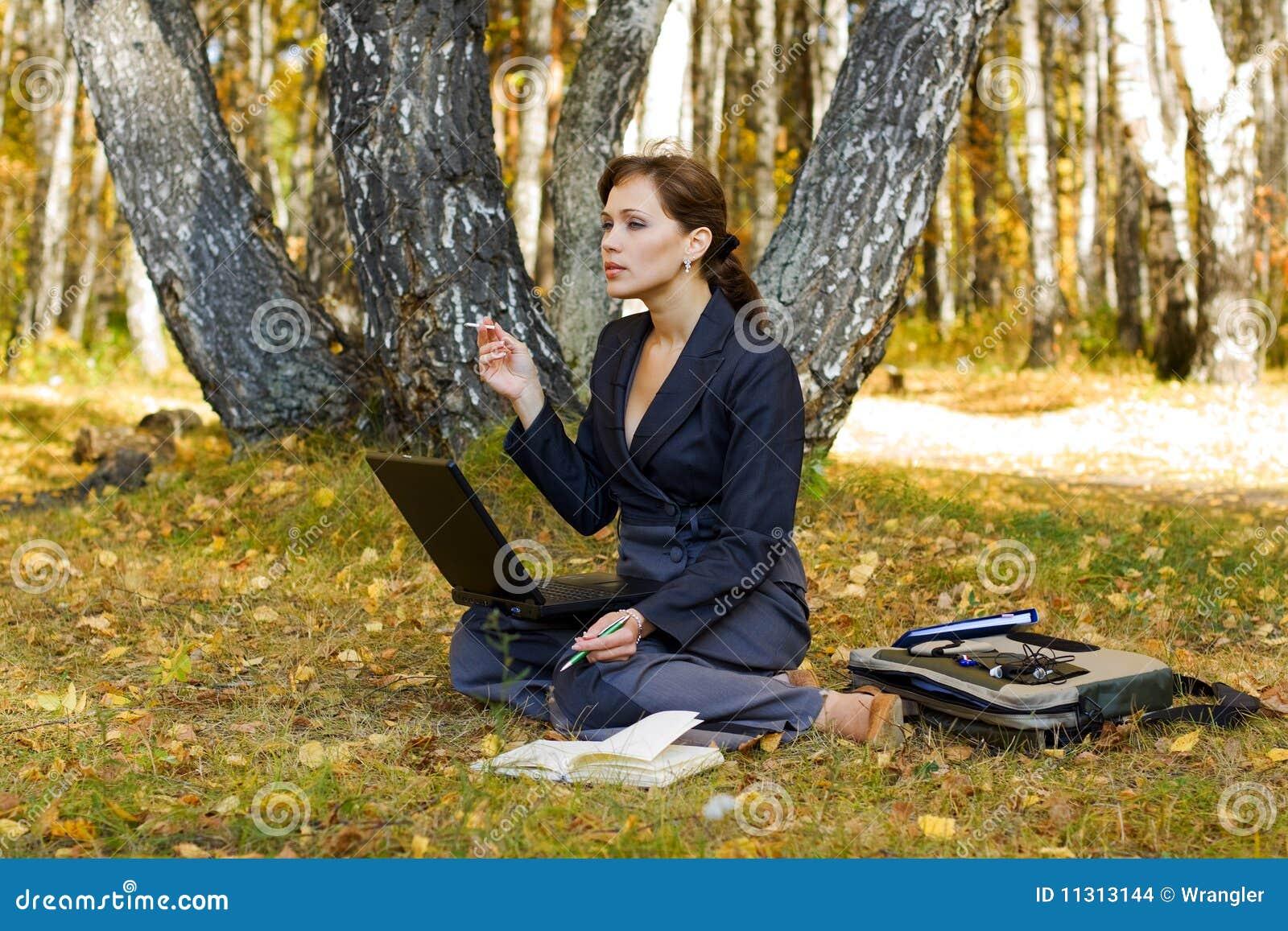 Junge Geschäftsfrau im Wald.