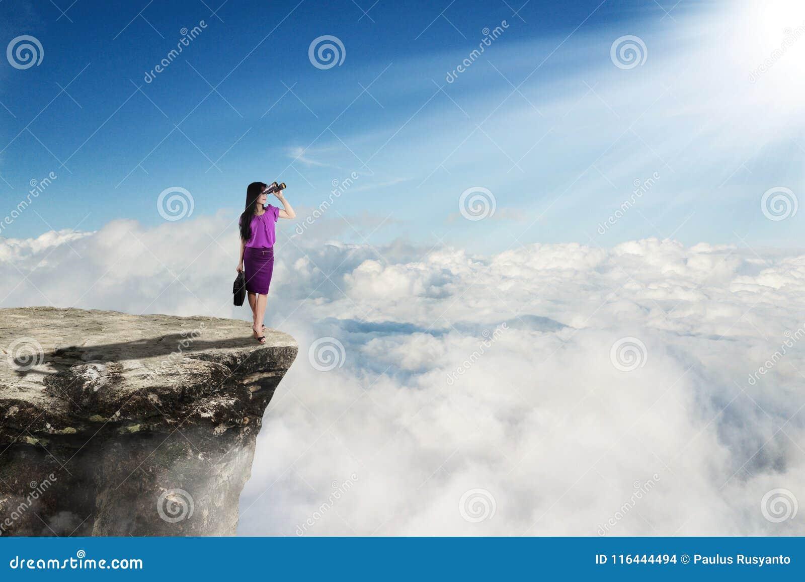 Junge Geschäftsfrau mit Ferngläsern auf Klippe