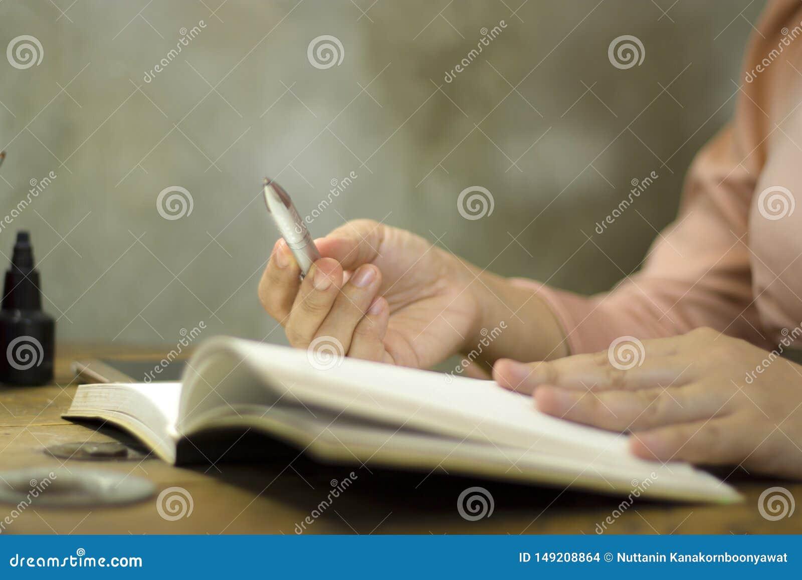 Junge Gesch?ftsfrau, die mit einem Stift im B?ro, sie ?ber die Zeit hinaus bleibend arbeitet