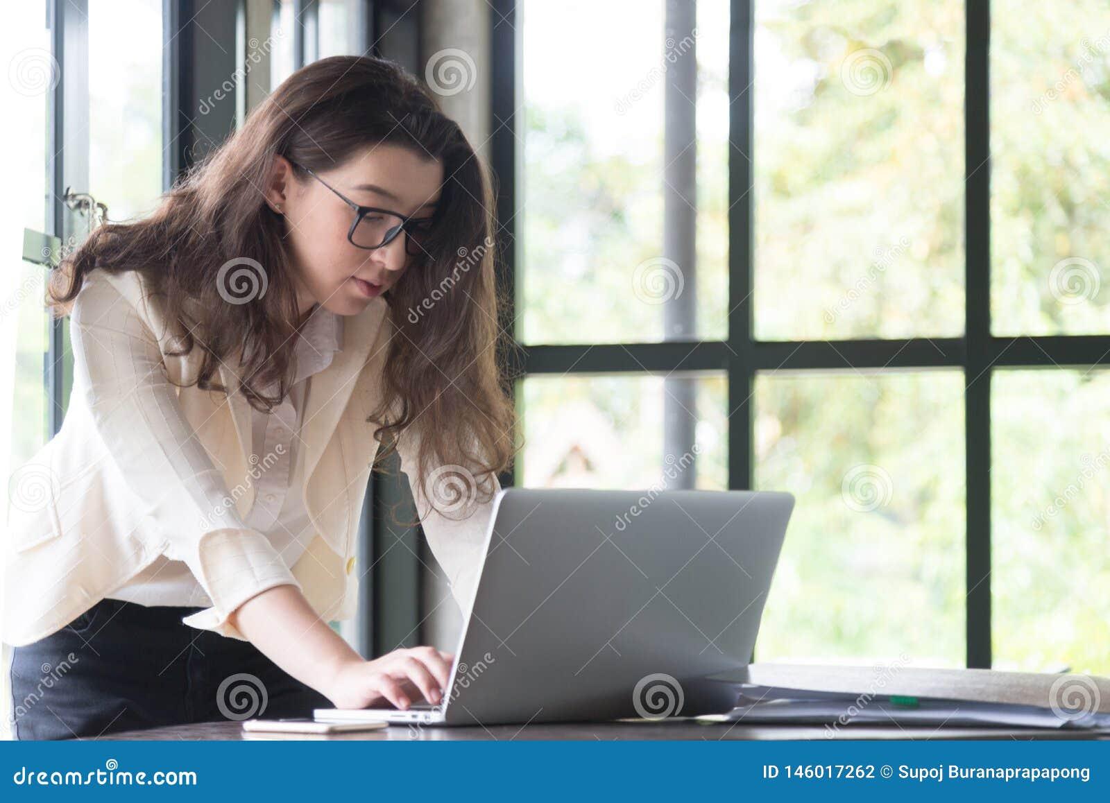 Junge Gesch?ftsfrau ihre Schreibenmassage des Laptops zu ihrem Kunden am Arbeitsplatz verwenden On-line-Einkaufsinternet-Gesch?ft