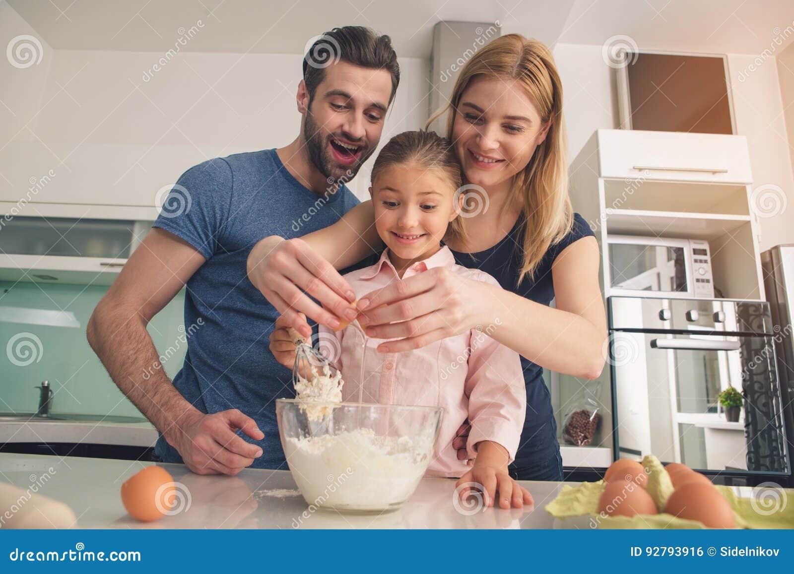 Junge glückliche Familie, die den zusammen mischenden Teig kocht