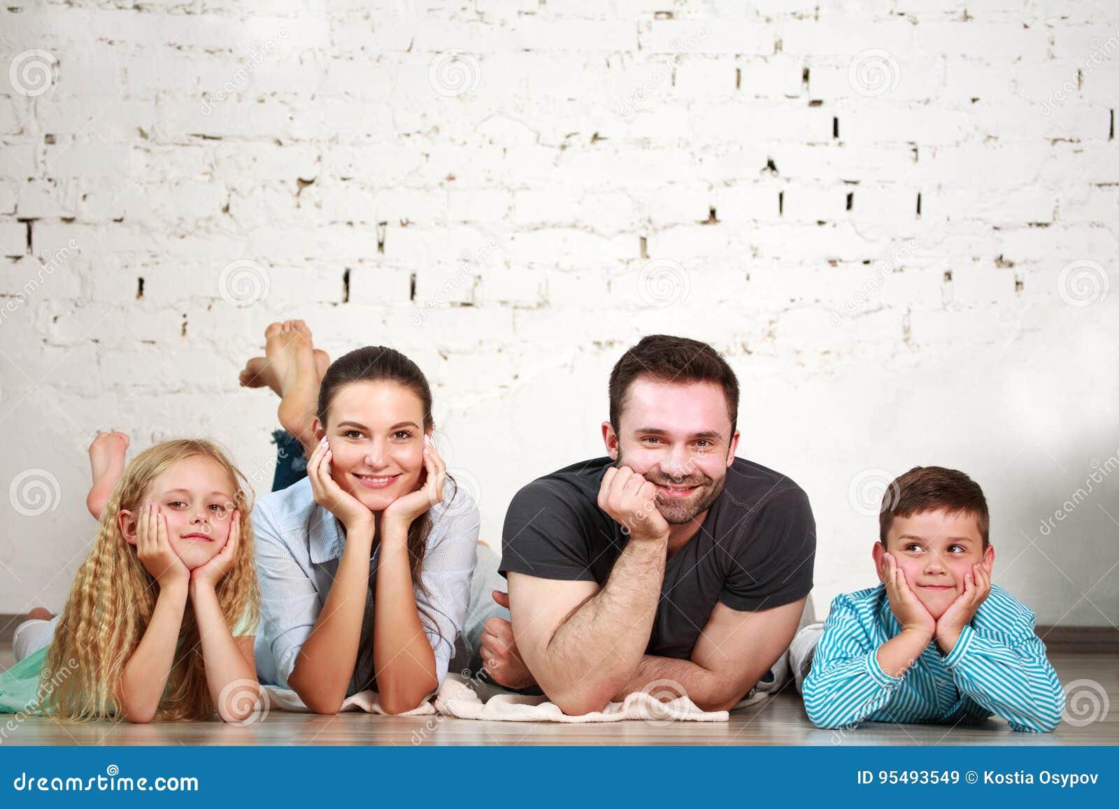 Junge glückliche Familieneltern und zwei Kinder steuern Studio automatisch an