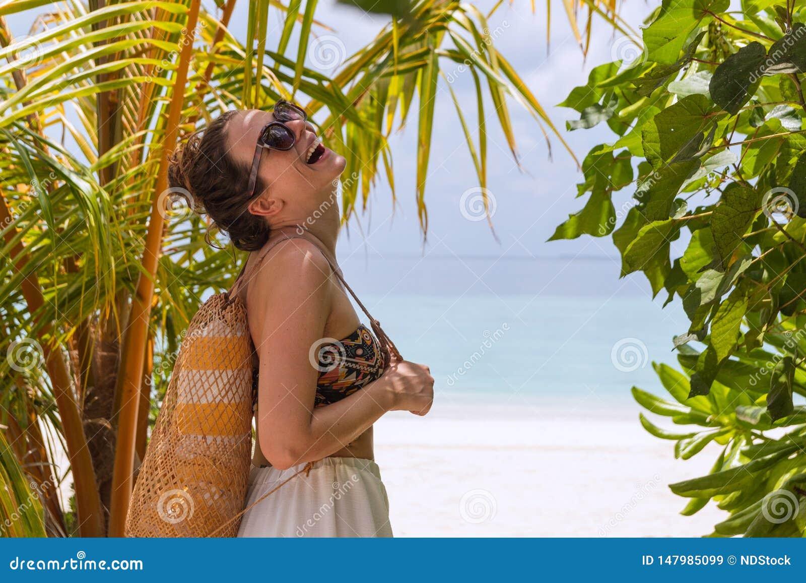 Junge glückliche Frau mit einem Tuch gehend zum Strand in einem tropischen Bestimmungsort Lachen zur Kamera