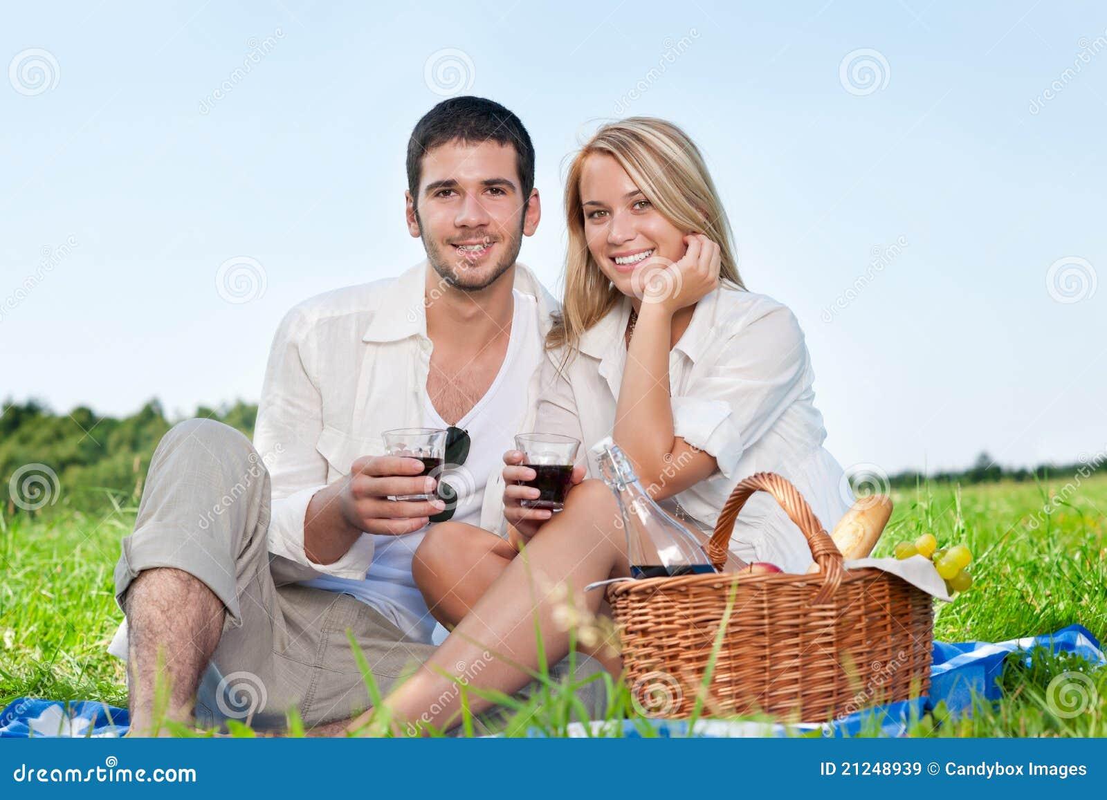 Junge glückliche Paare des Picknicks, die mit Wein feiern