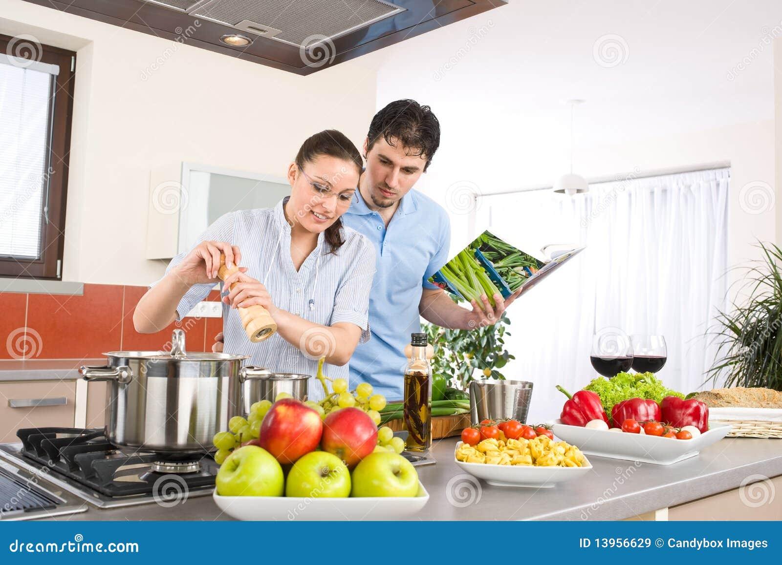 junge gl ckliche paare kochen in der k che mit kochbuch stockbild bild 13956629. Black Bedroom Furniture Sets. Home Design Ideas
