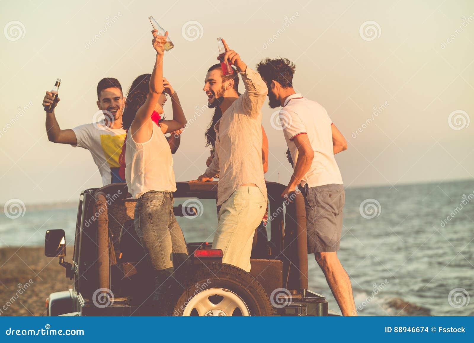 Junge Gruppe, die Spaß auf dem Strand hat und in ein konvertierbares Auto tanzt