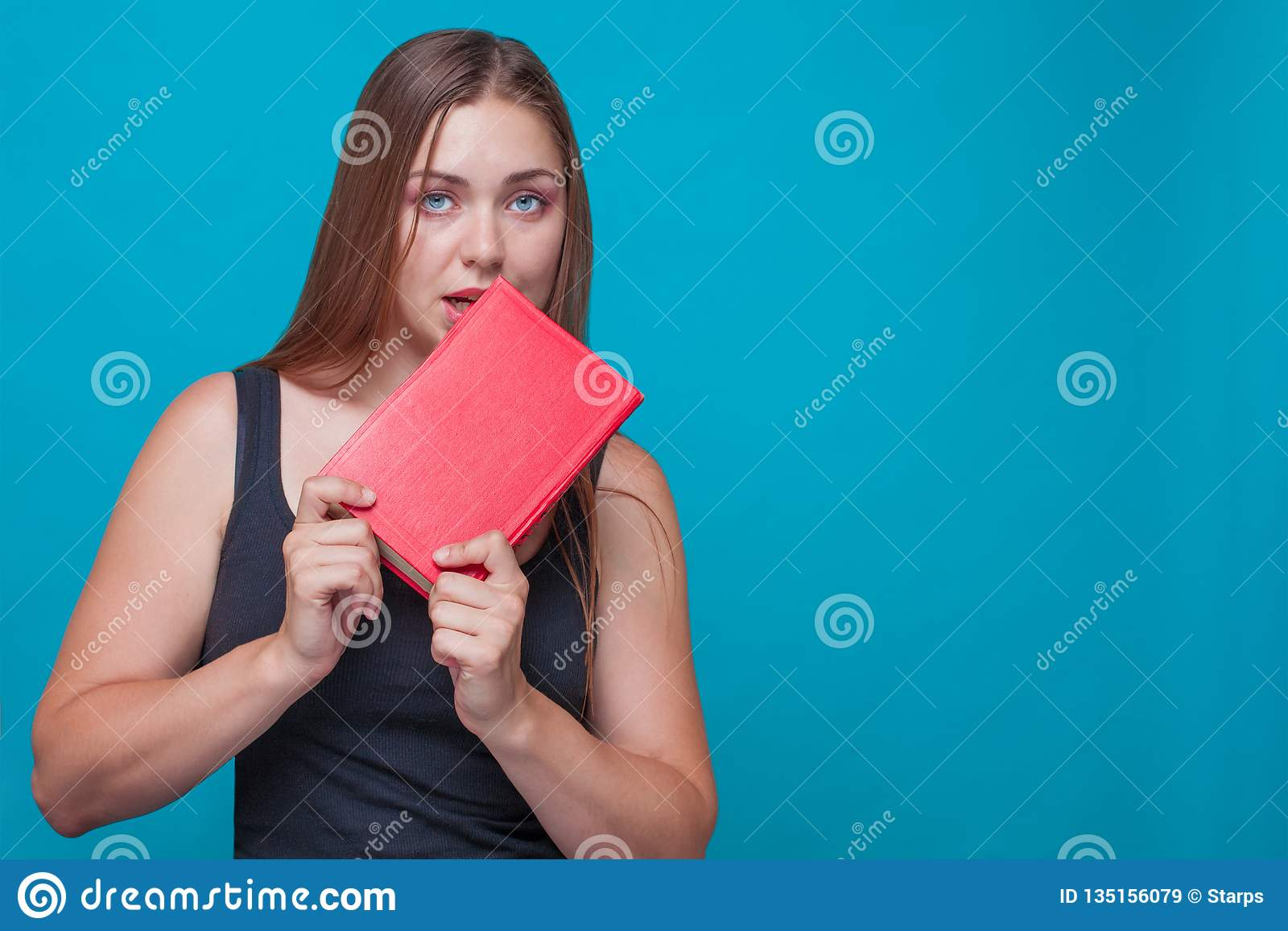 Junge hübsche Frau beißt ein rotes Buch, das in ihren Händen hält,