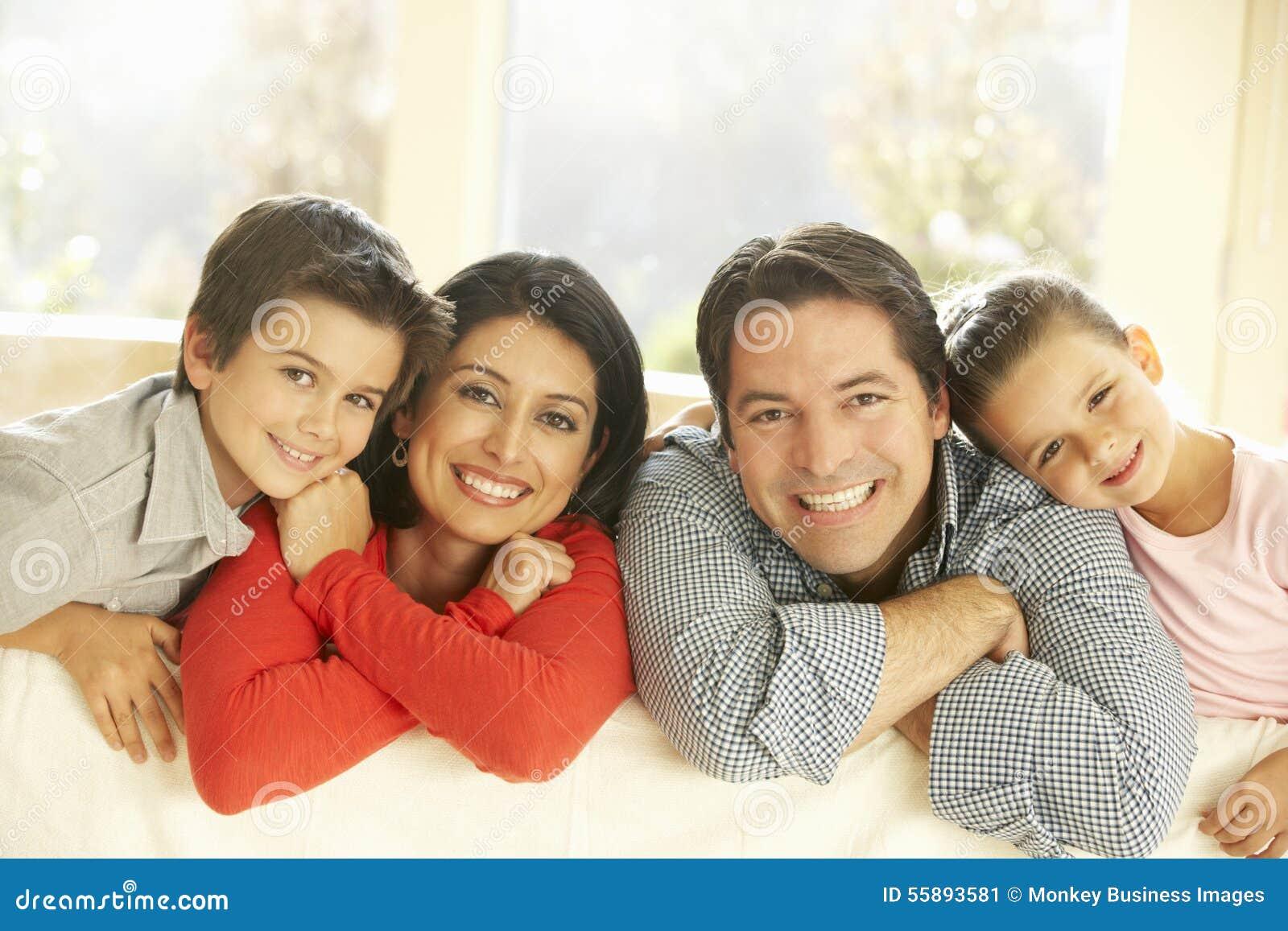 junge hispanische familie die auf sofa at home sich. Black Bedroom Furniture Sets. Home Design Ideas