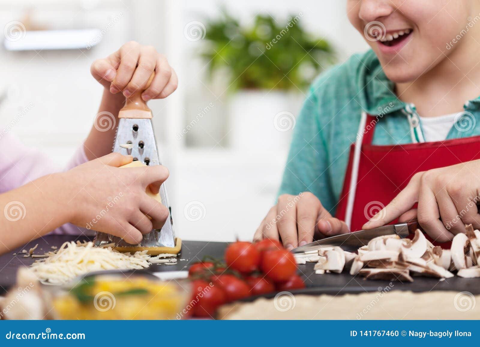 Junge Jugendlichhände bereiten eine Pizza in der Küche zu -, die oben nah ist