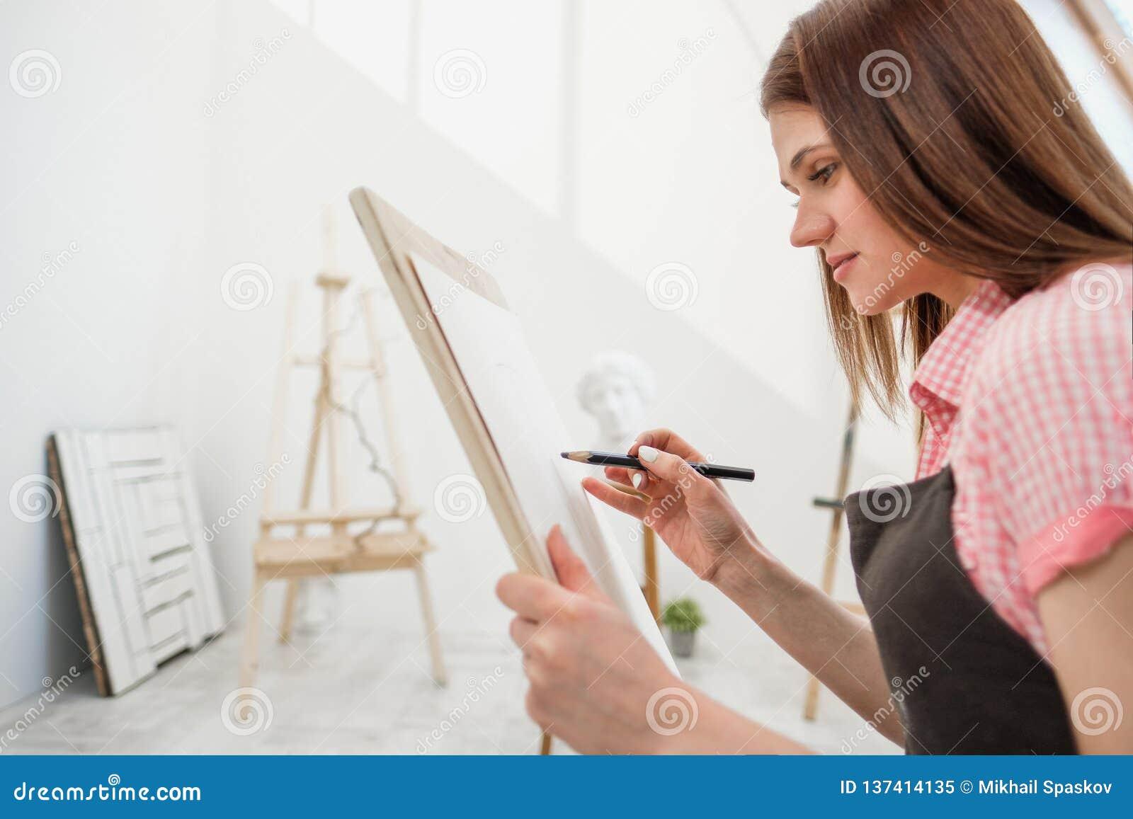 Junge Künstlerin zeichnet einen Bleistift auf Segeltuch